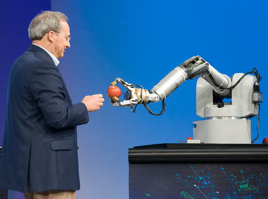 Rattner eyes an apple grasped by a robot that senses nearby objects through changes in the surrounding electromagnetic field.