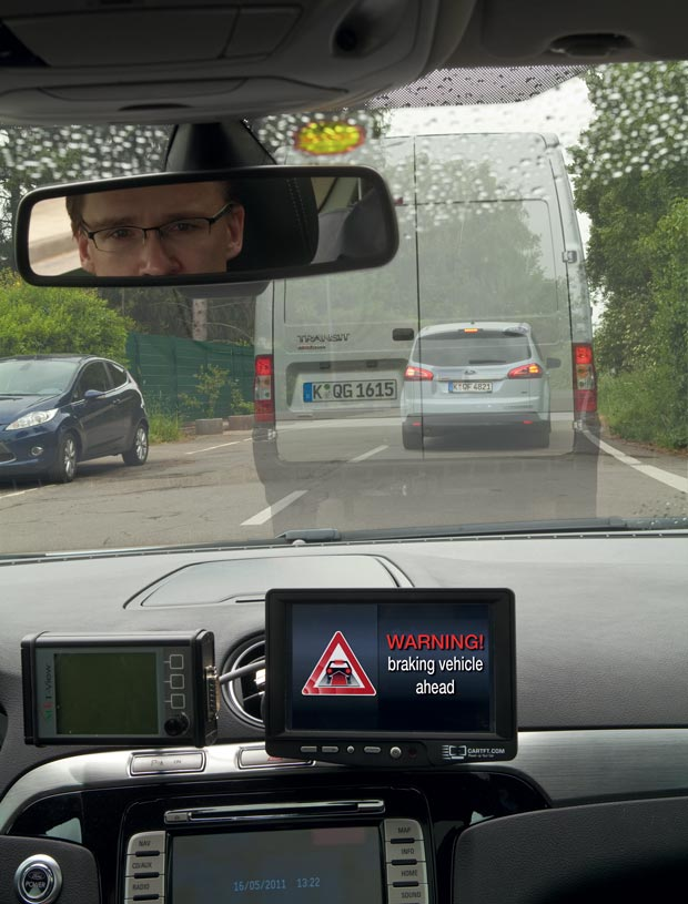 This illustration shows one advantage Ford sees for vehicle-to-vehicle communication: your car could detect abrupt braking of a car ahead that's blocked by a large van.