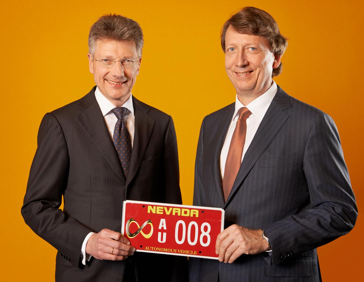 Continental CEO Elmar Degenhart and CFO Wolfgang Schaefer hold a red license plate that gives them permission to test autonomous vehicles in Nevada.