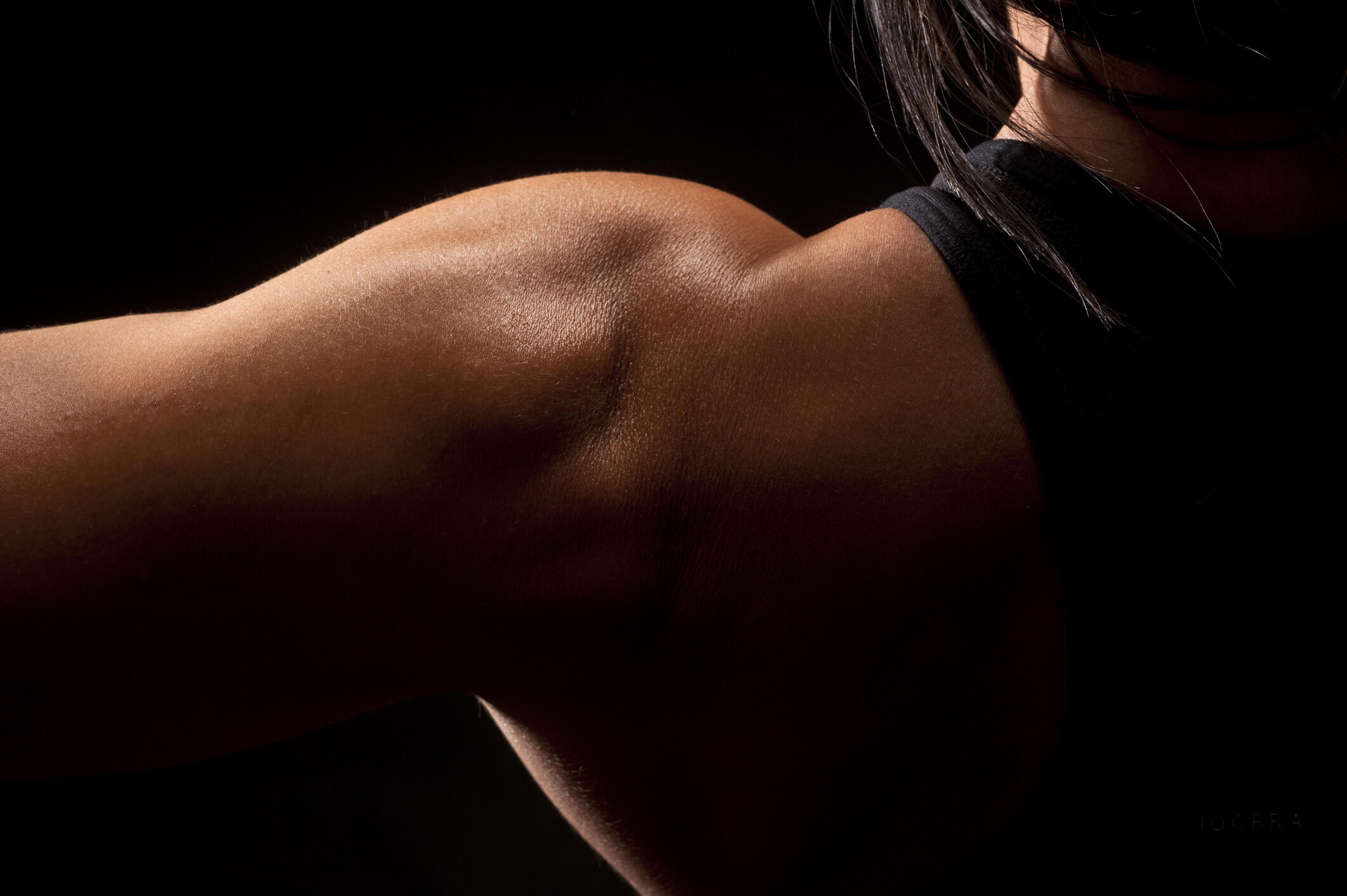 close up of a woman's strong shoulder muscles in low lighting gettyimages-154888824