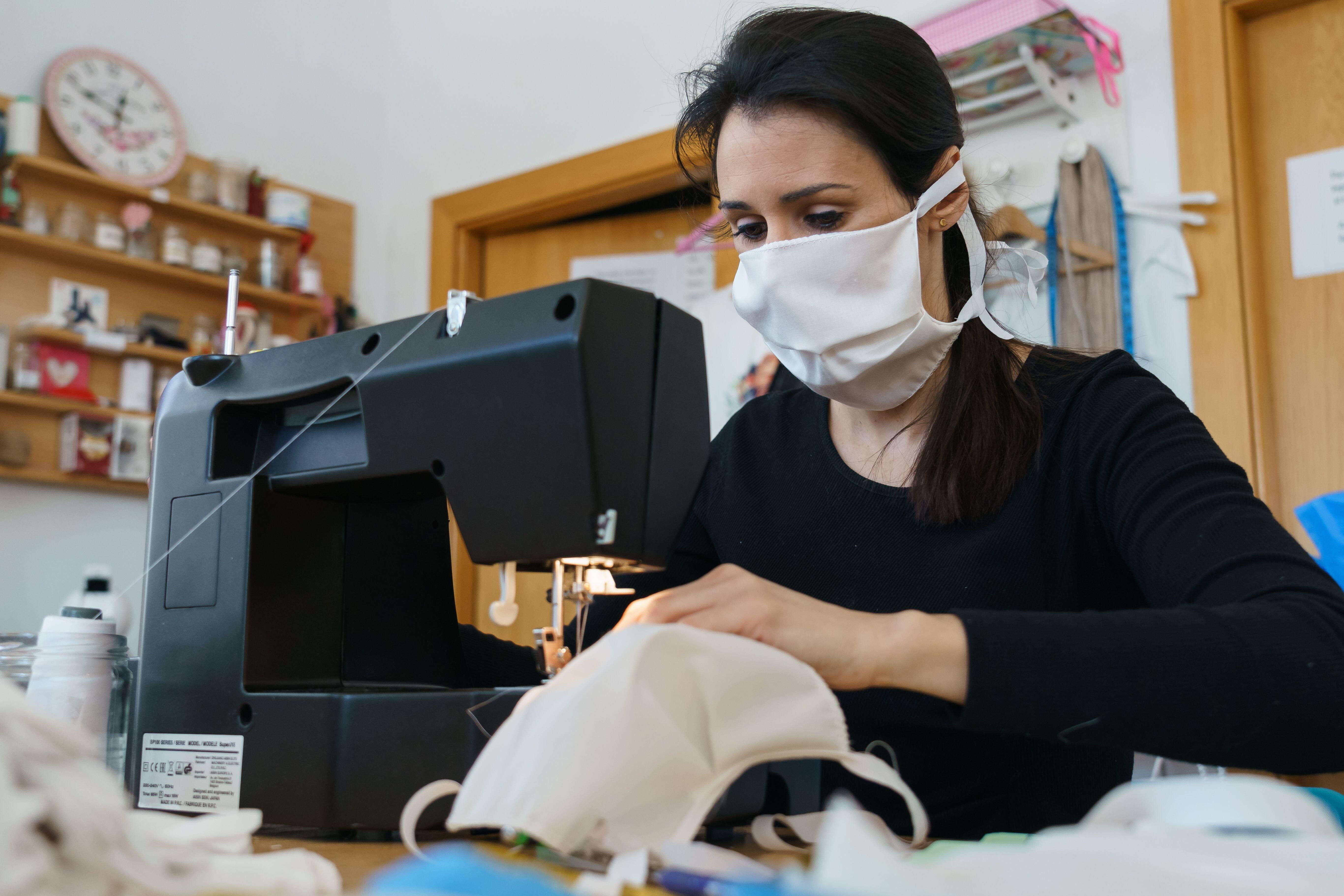 A woman sewing handmade face masks in Spain last month. The US Centers for Disease Control and Prevention now recommends that people in the states wear nonmedical, cloth face masks when they leave home. But medical-grade masks, like N95 respirators, shoul