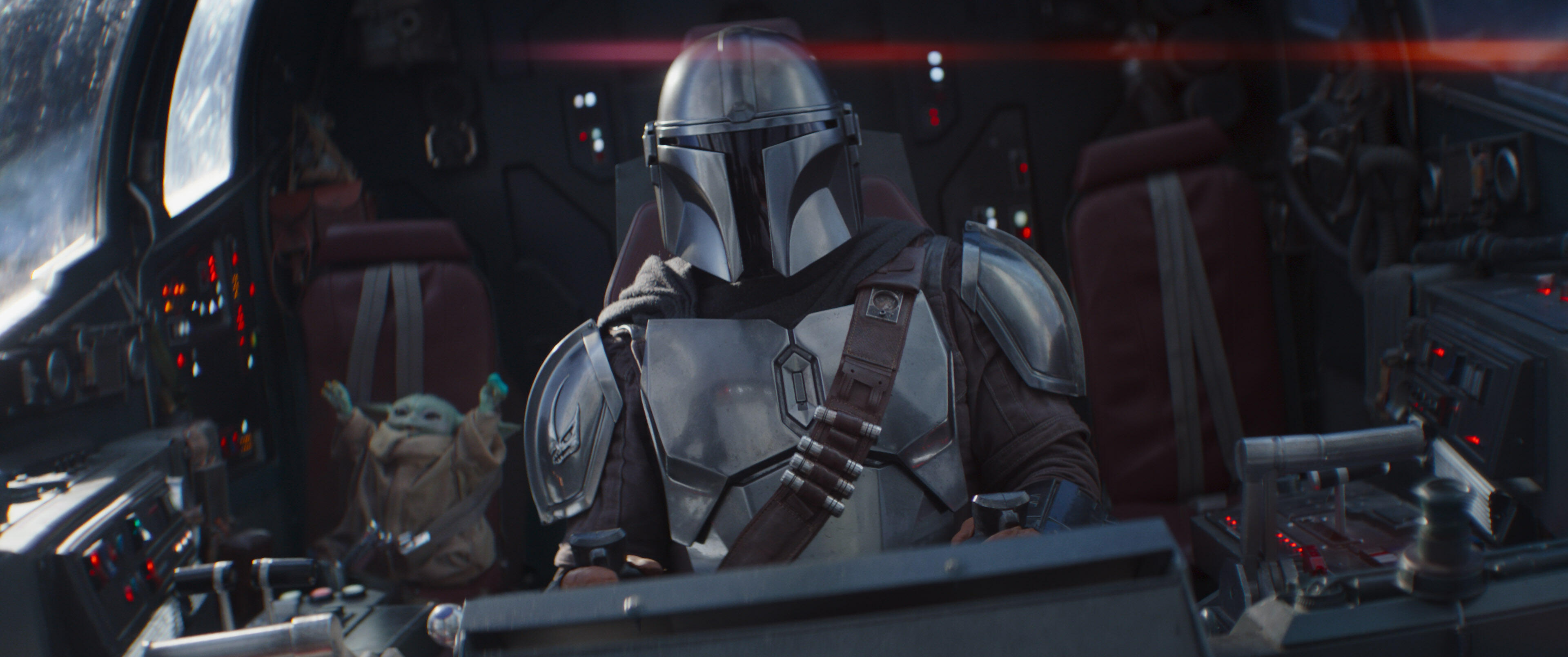 The Mandalorian pilots a spacecraft, with Baby Yoda sitting nearby.
