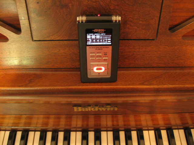 Photo of the Edirol R-09HR portable recorder sitting on a piano.