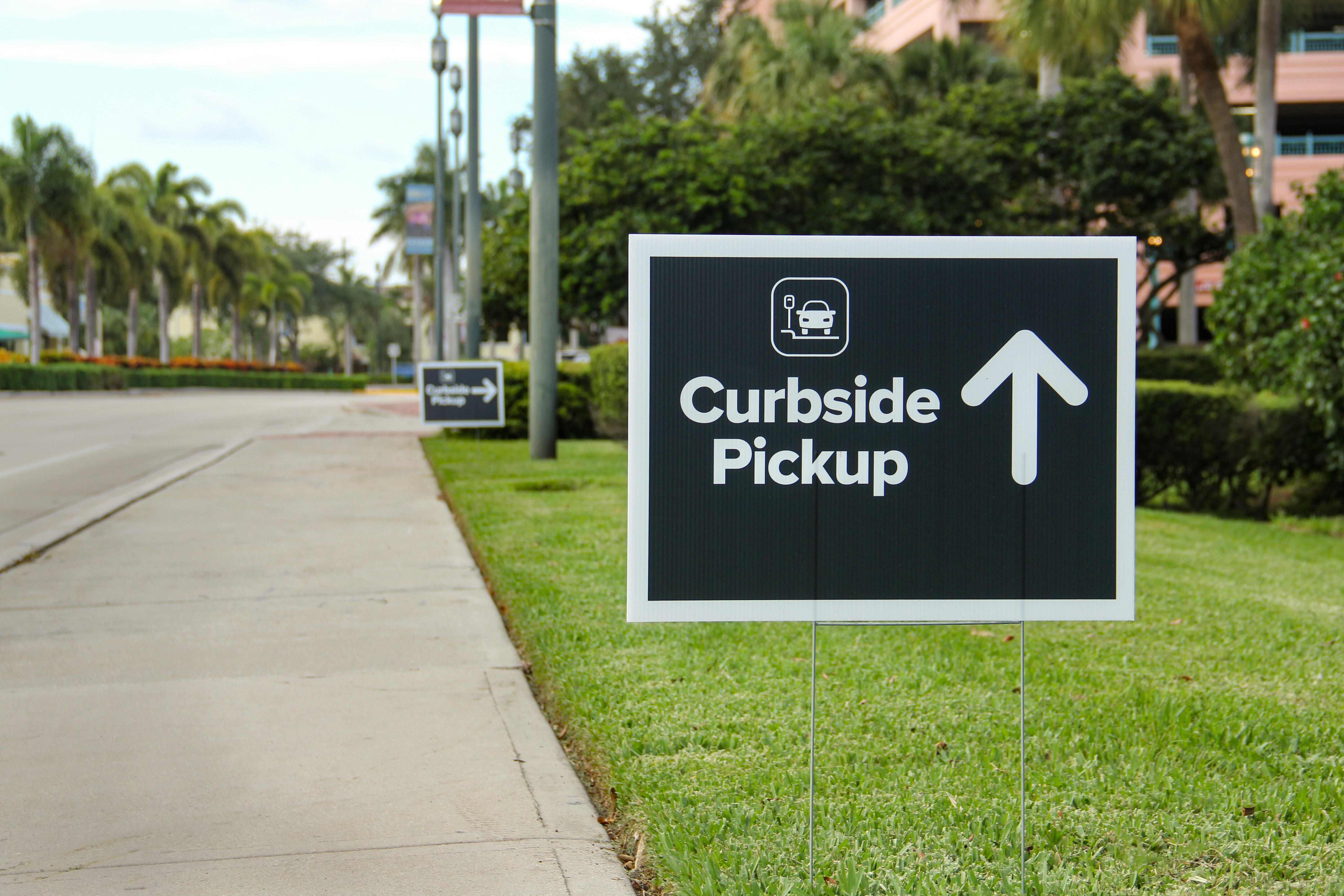 A sign on a parking strip points to the curbside pickup area at a parking lot.