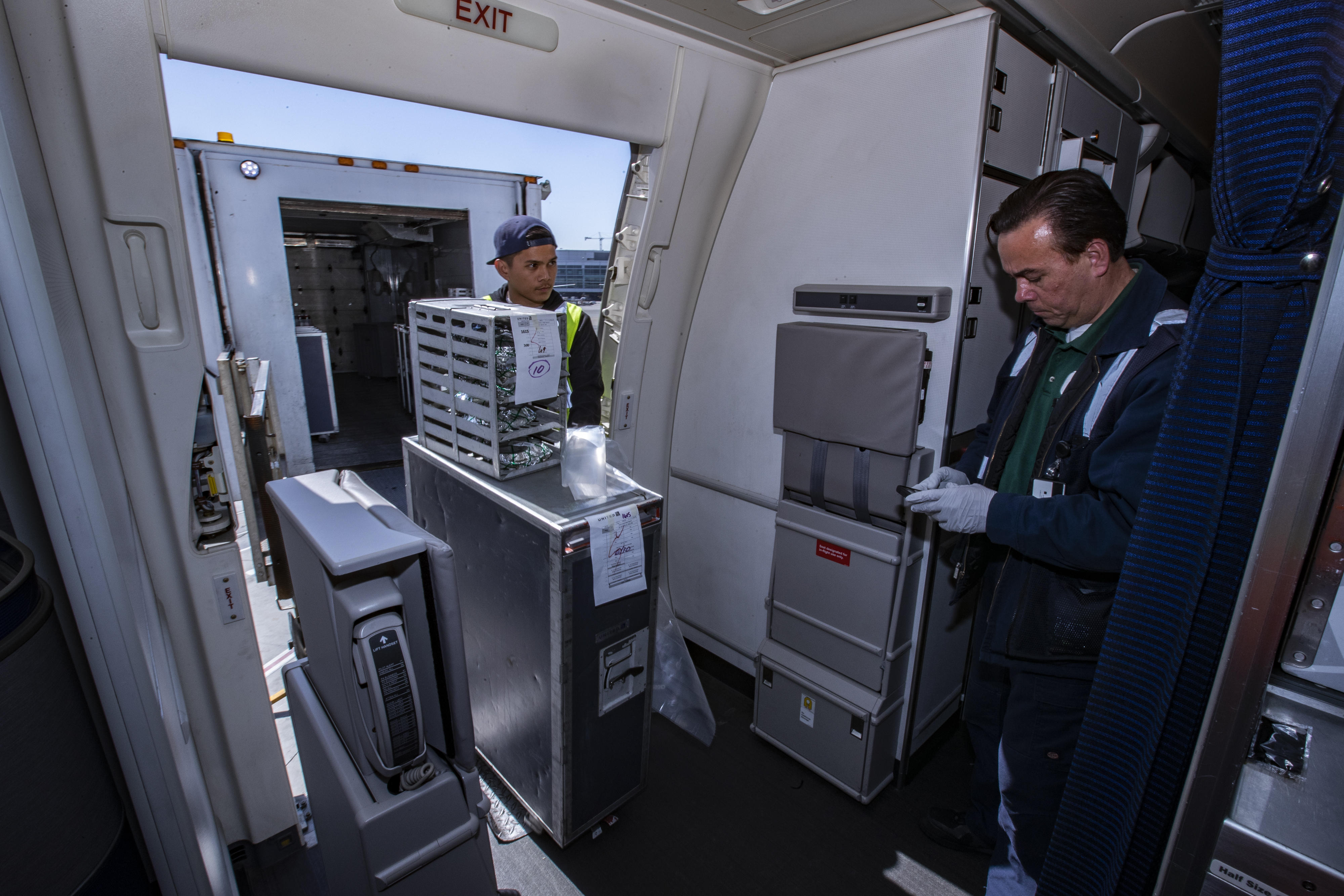 Before the new passengers board, catering crews load food onboard and remove used carts and rubbish from the previous flight.