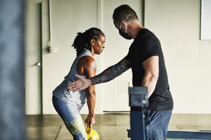 Personal trainer and client holding kettlebell at a gym