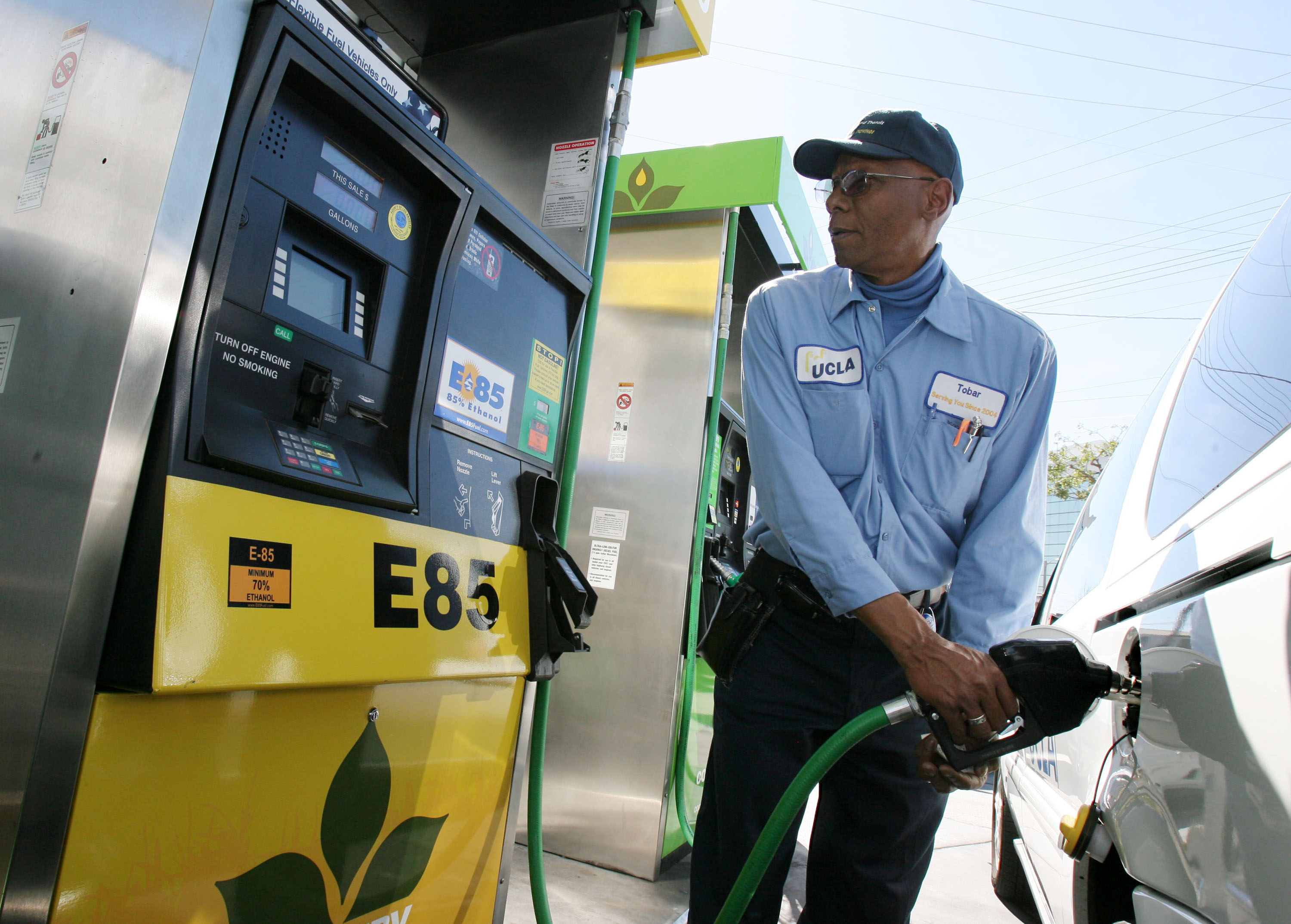 A gas station attendant fuels an E85 capable vehicle