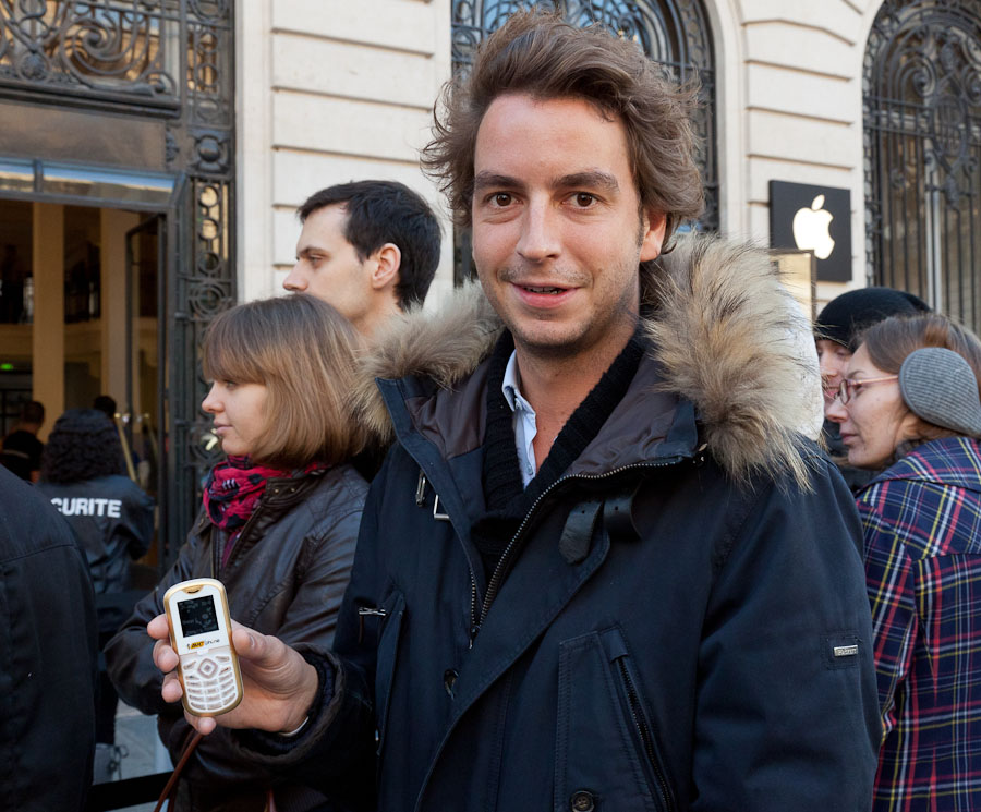 "Paris resident Raphael Journé, about to buy his seventh iPhone, shows the ""crappy"" phone he's been suffering during a two-week period after he lost his iPhone 4 and before Apple's latest smartphone went on sale."