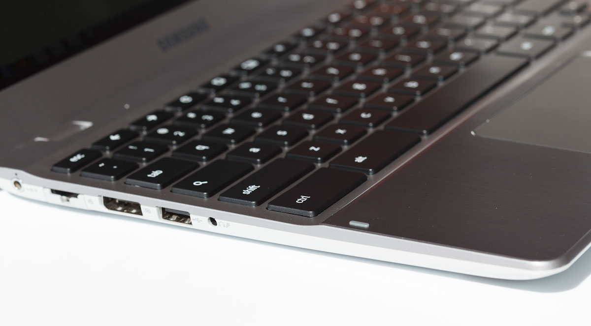 The Series 5 550 Chromebook's keys are recessed in a shallower section behind a brushed-metal wrist rest area. On the left side of the laptop are a headphone port, a USB port, an Ethernet port, and a DisplayPort video port. On the other side are another U