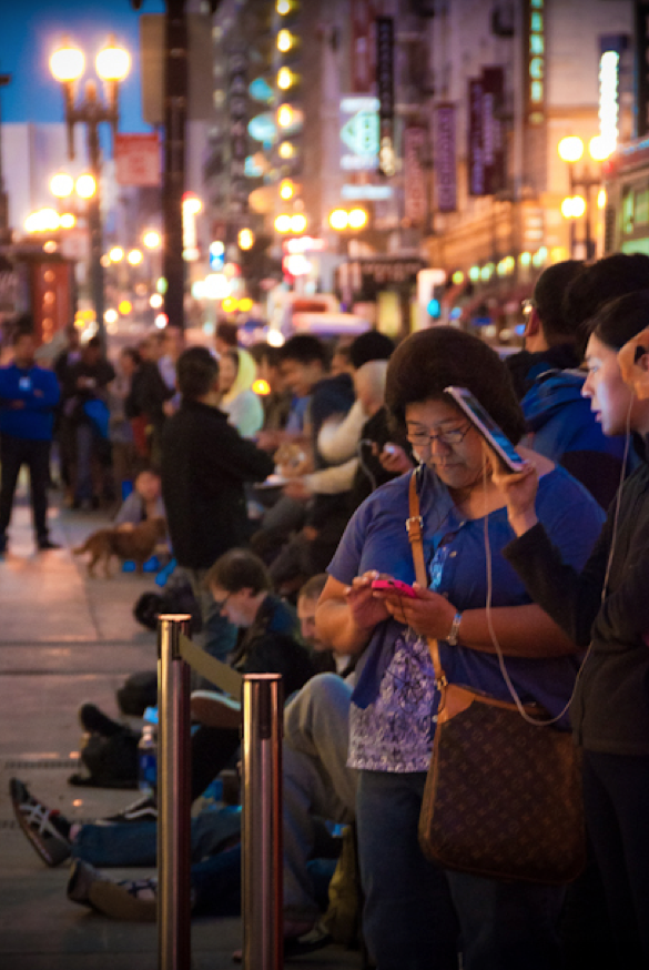 Line-goers wait in an early morning queue for Apple's iPhone 4S last October.