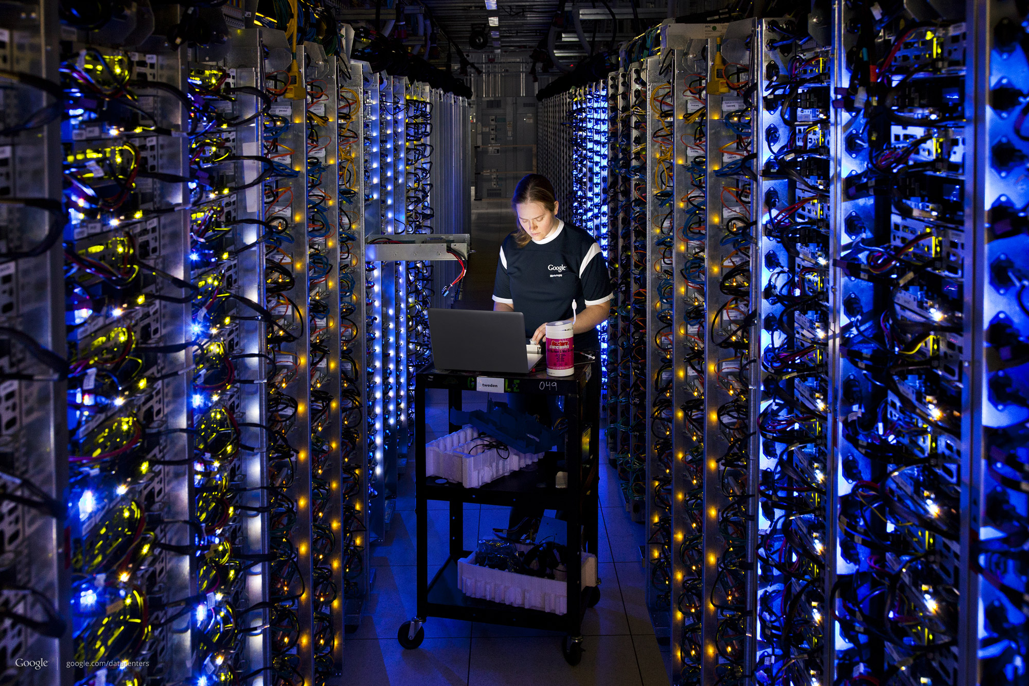 Denise Harwood diagnoses an overheating CPU inside a long aisle between racks of computing gear in a Google data center.