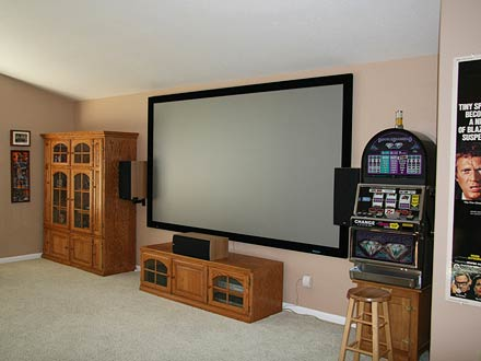 """We already have a more standard TV room downstairs, with a 50-inch Panasonic plasma, Oppo DVD player, Onkyo TX-674 Receiver, DirecTV H-20 HD satellite receiver, and Omni Nanosat speakers. I wanted what my wife calls a 'man's room' and it's truly my dream room. I went from a 60-inch Sony LCD TV to the 123-inch screen because I love to entertain our family and we enjoy watching movies--but we don't necessarily want to go the the theater. It is the focal point whenever we have have people over or host family parties. Now everyone wants to have their birthday parties at our house."""