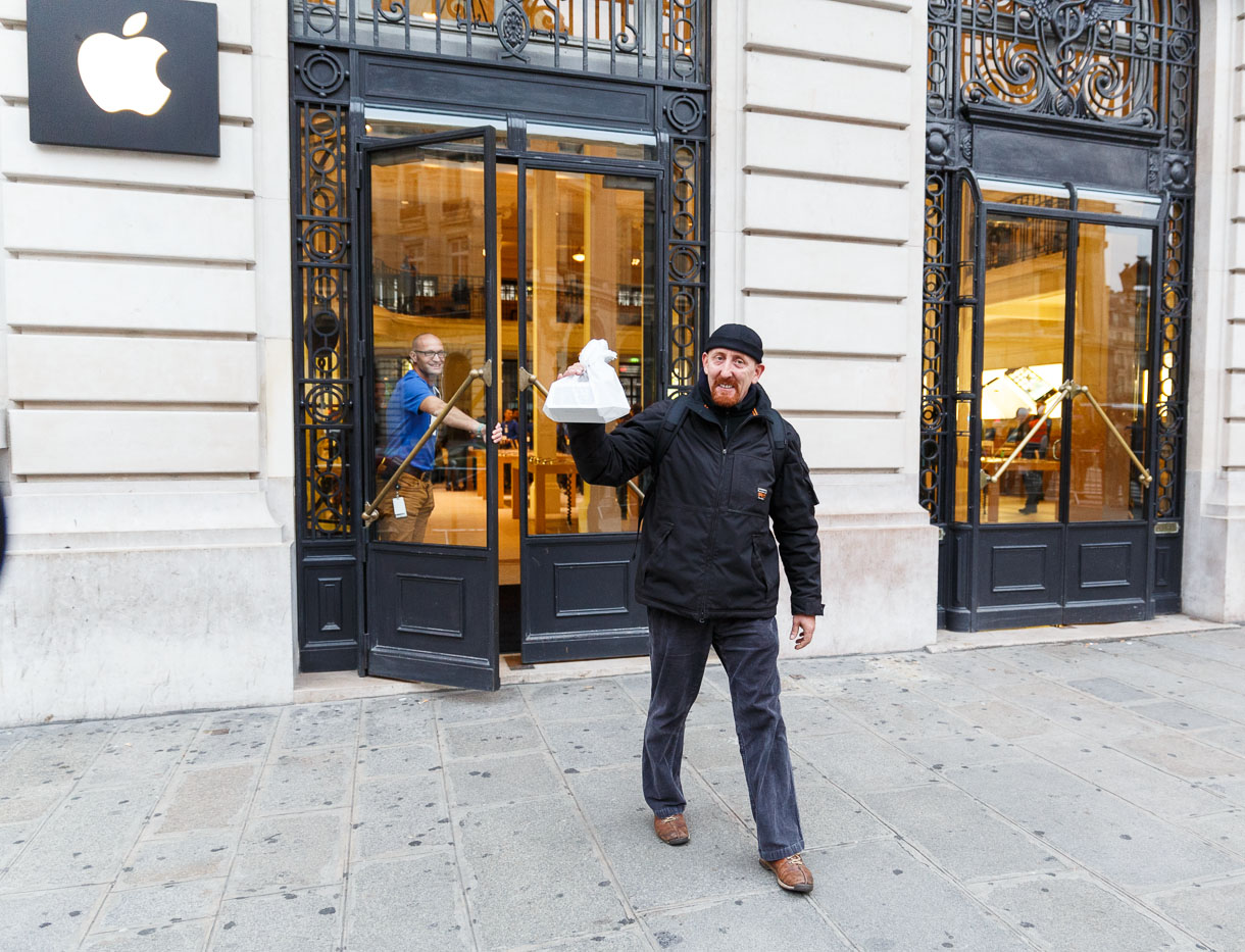 Sylvain Gautier emerges from the Apple store in Paris at 8:03 a.m. local time Friday after becoming the first in France to buy an iPhone 5S, Apple's new flagship smartphone. He bought a second for a friend.