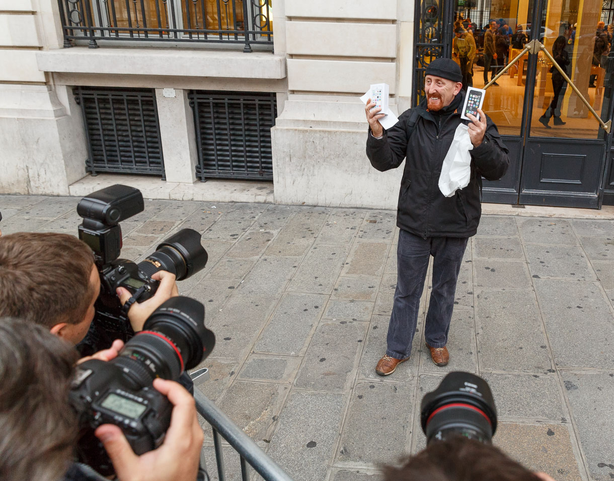 Sylvain Gautier, the first member of the French public to own an iPhone 5S, shows off his purchase for press photographers outside Apple's Opera store in Paris. Apple's iPhone 5S and the lower-end 5C went sale Friday morning in several countries.