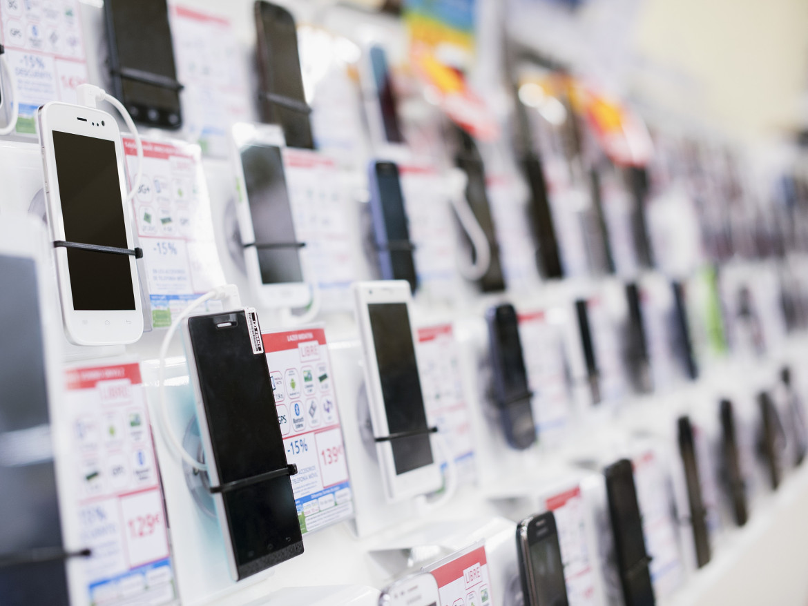 Many different smartphones on display at a retailer.