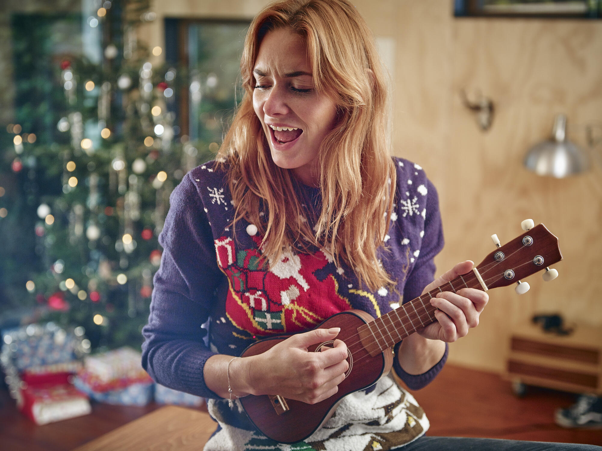playing a ukelele at home during the holidays
