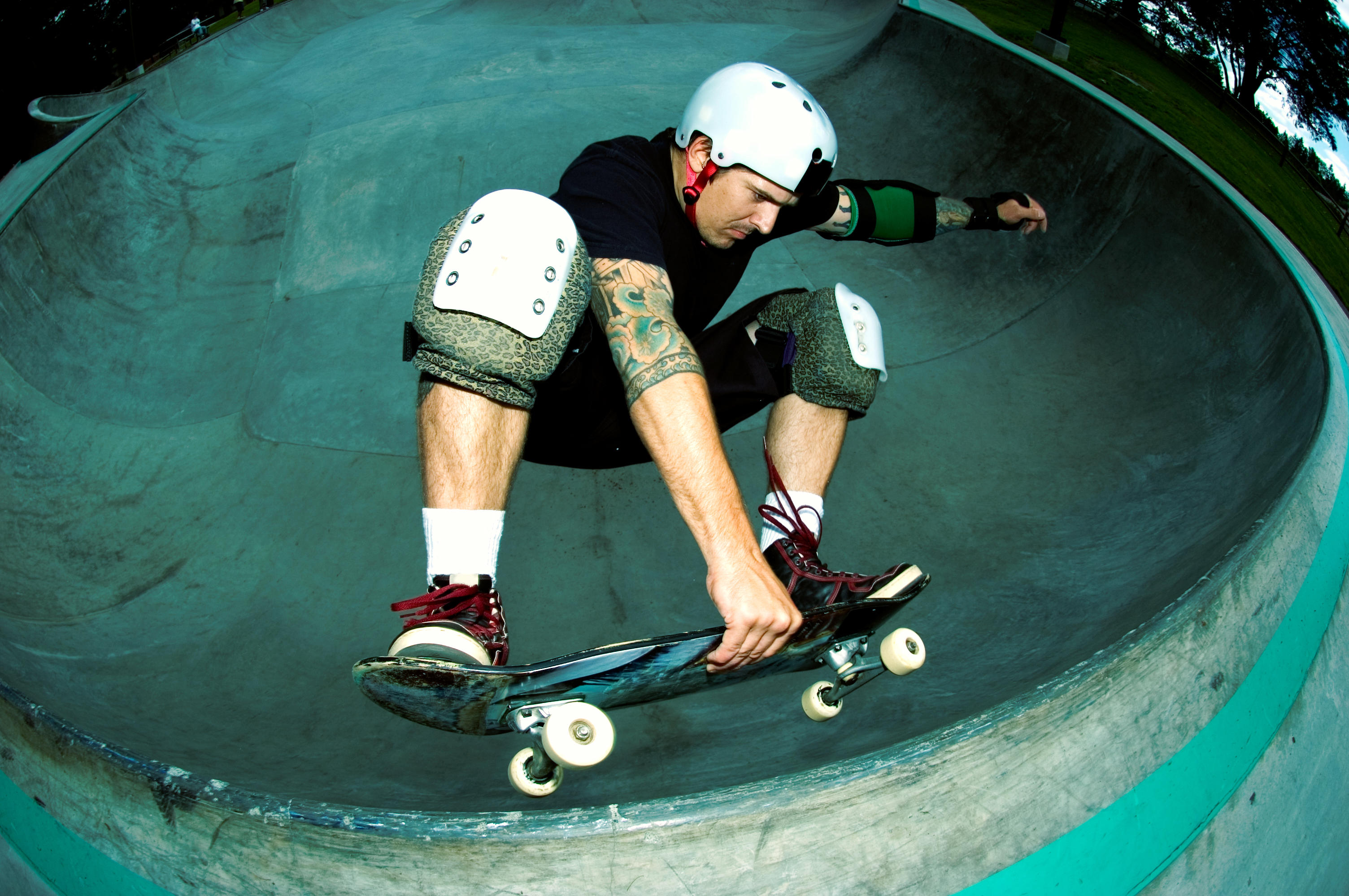 Male skateboarder performing a frontside air at a skateboard park. Cross-processed fish-eye image.