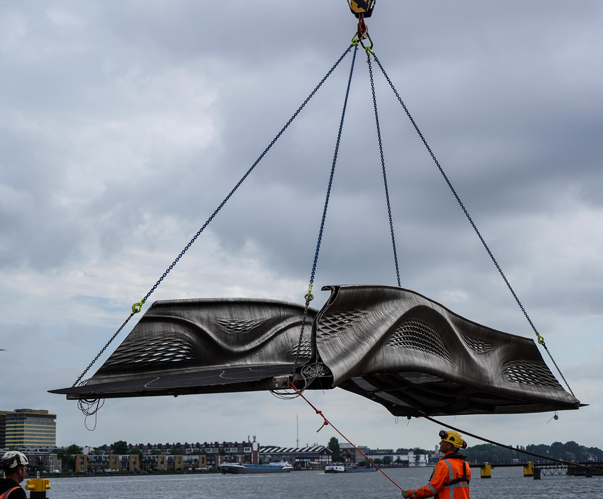 <p>The world's first 3D printed pedestrian bridge is hoisted off its transport as it makes its way to Amsterdam's Red Light District for installation.</p>