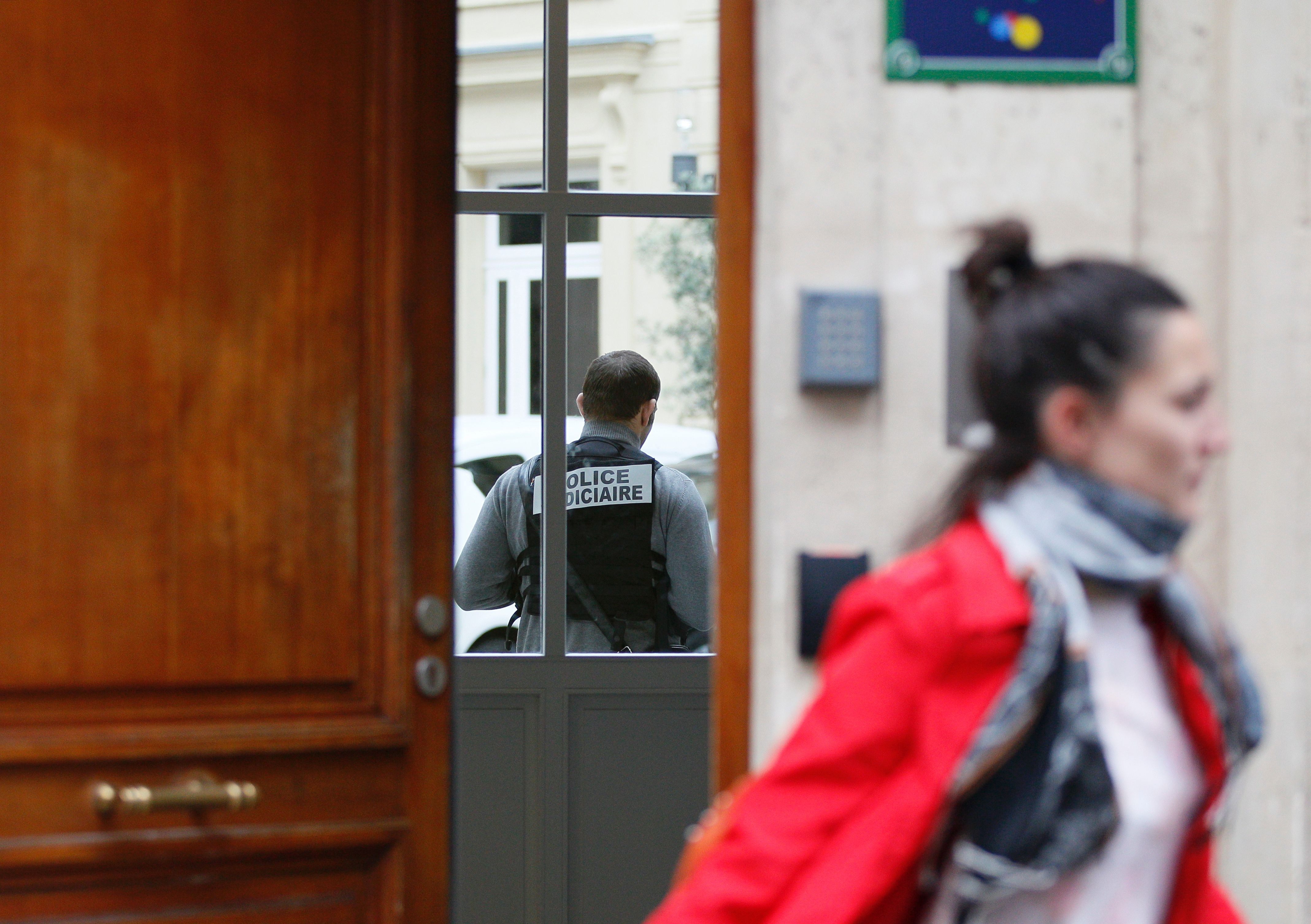 A police officer stands in the Paris offices of Google, as law enforcement carries out a search as part of a tax fraud investigation.