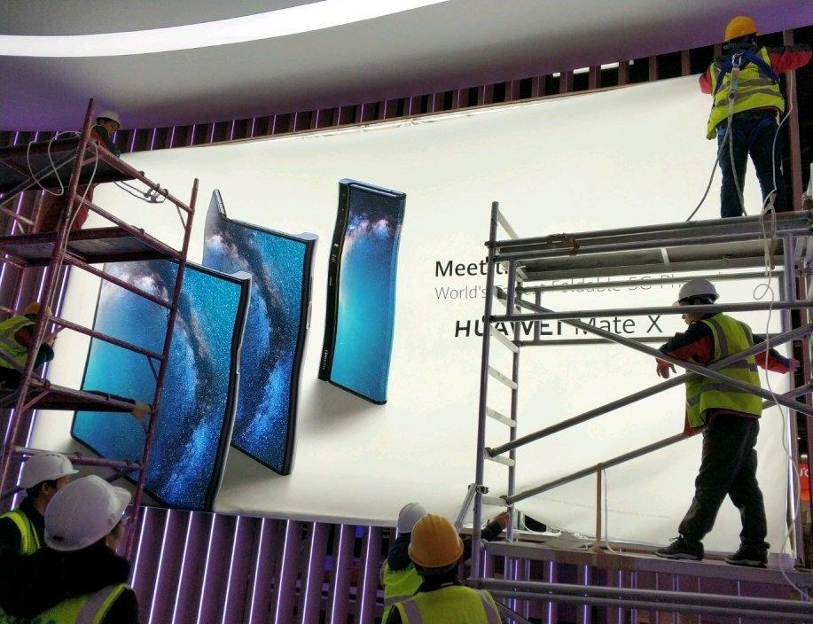 Workers putting up a billboard that purportedly shows Huawei's Mate X foldable phone.