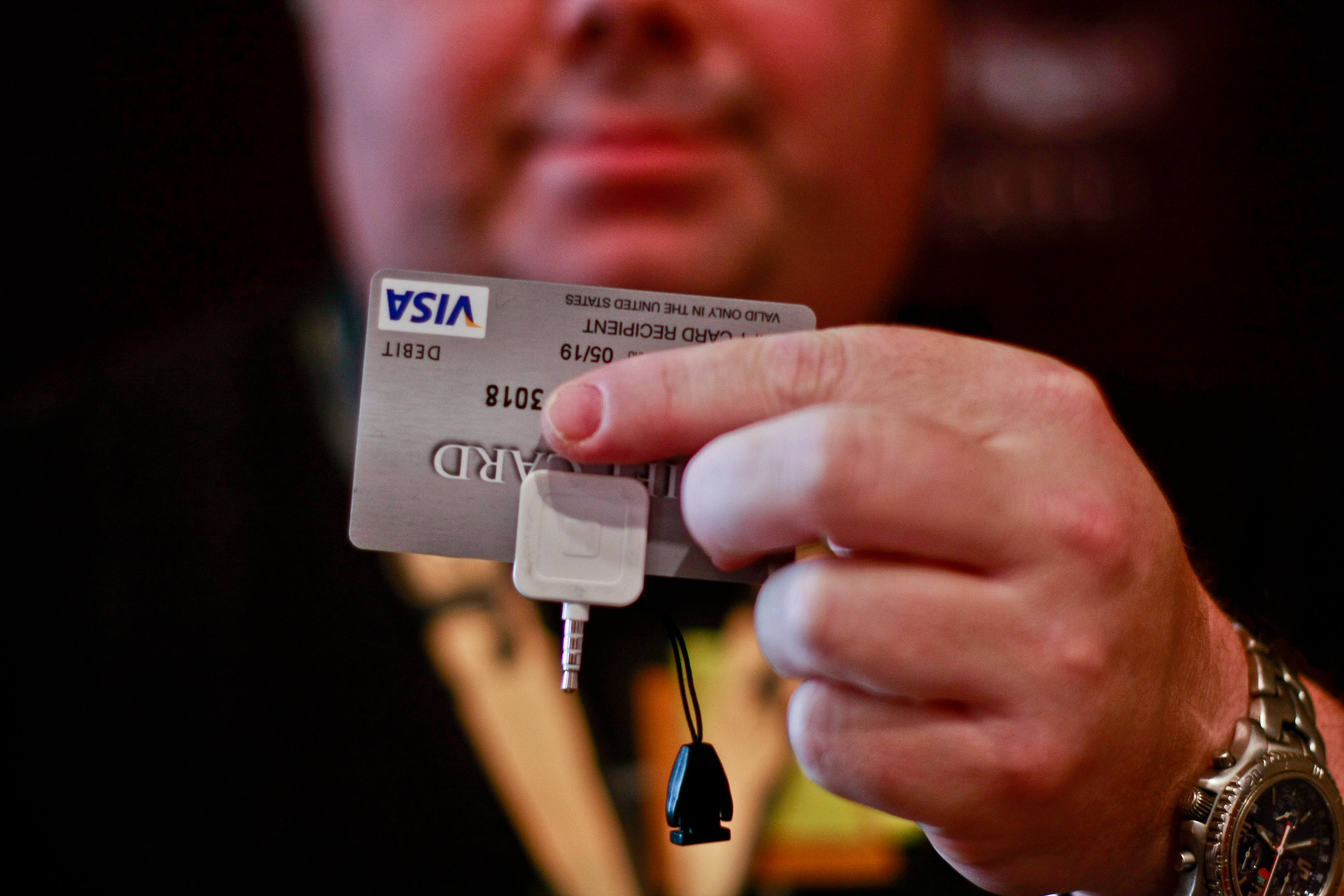 Zac Franken, director at Aperture Labs, holds up the Square device for processing credit cards with a mobile device. His company has just discovered two ways to steal credit card data using Square.