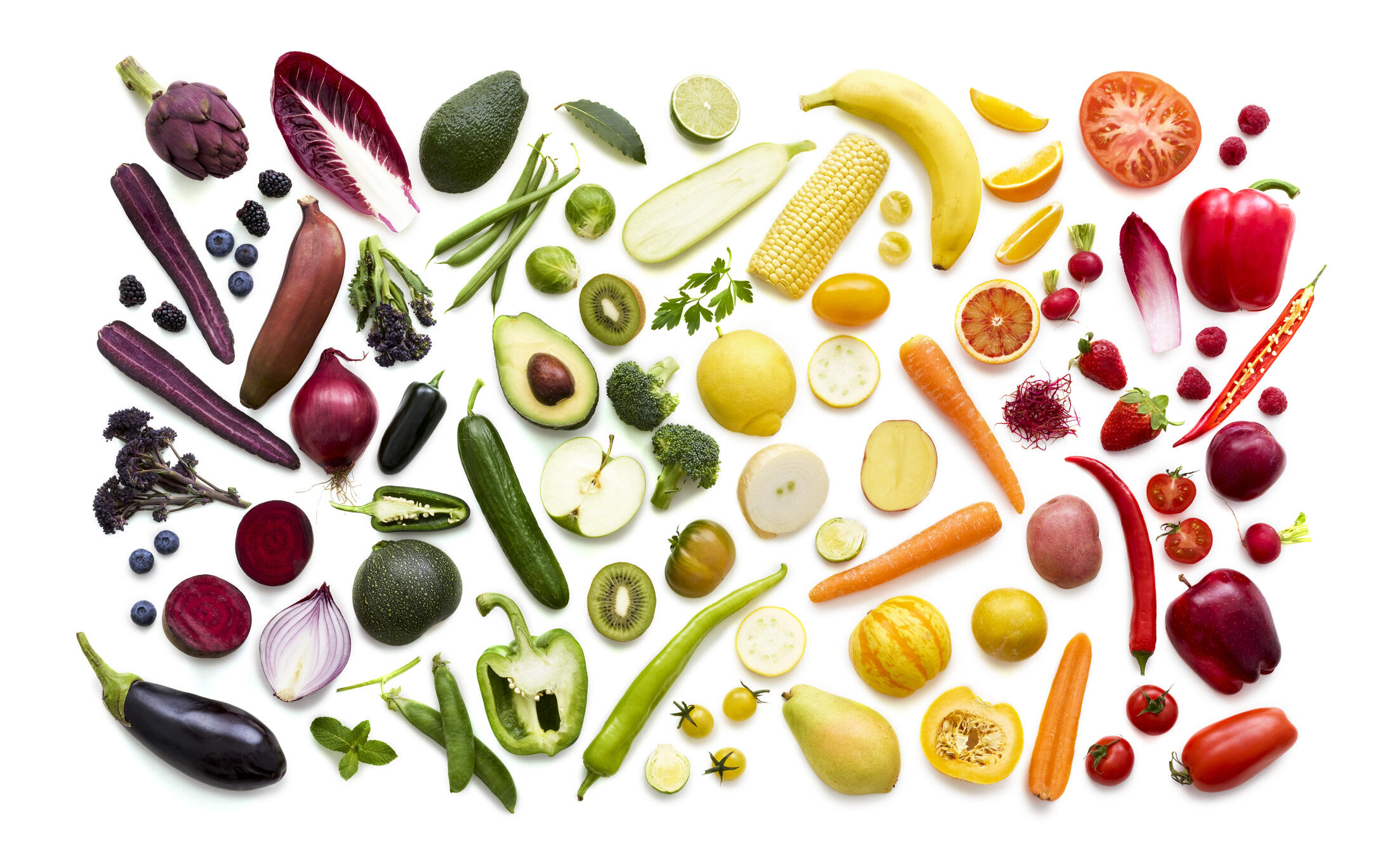 colorful fruits and vegetables on a white backround arranged in the order of the rainbow
