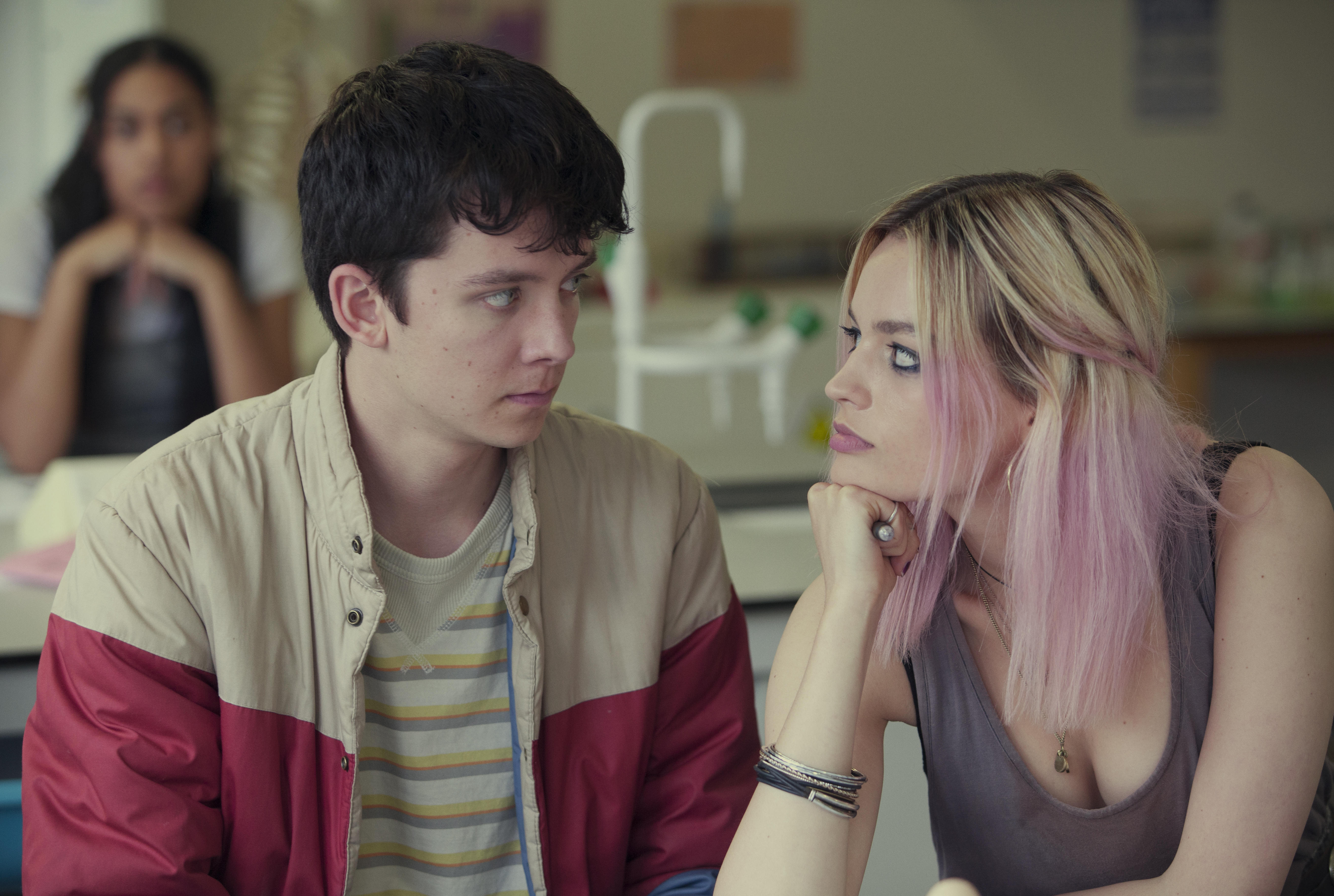Two characters from Sex Education look at each other seated at a table
