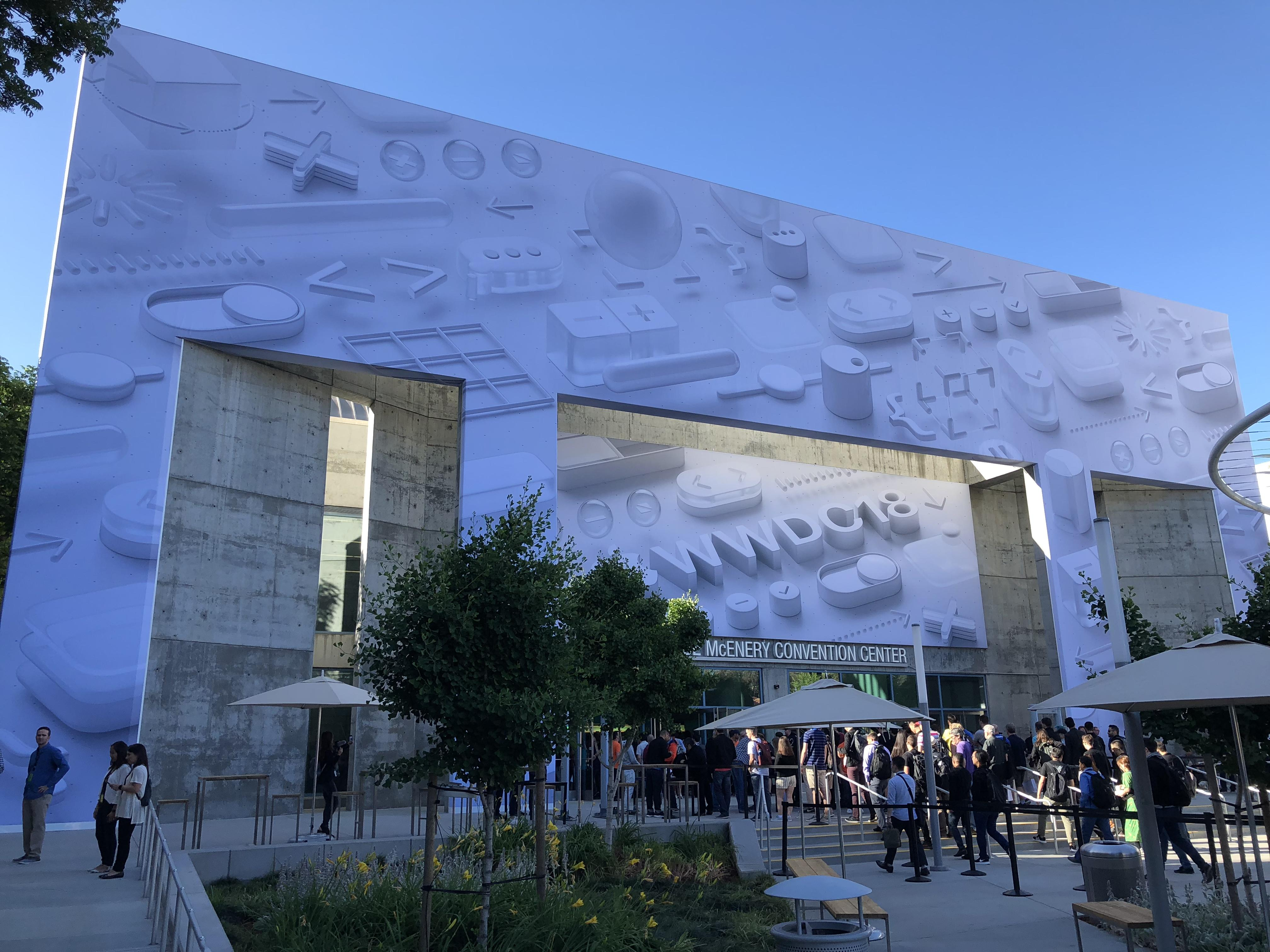 The exterior of the building outside the Apple event at dusk, with the logo superimposed over the outside wall of the structure and a banner hanging down over the main entrance.