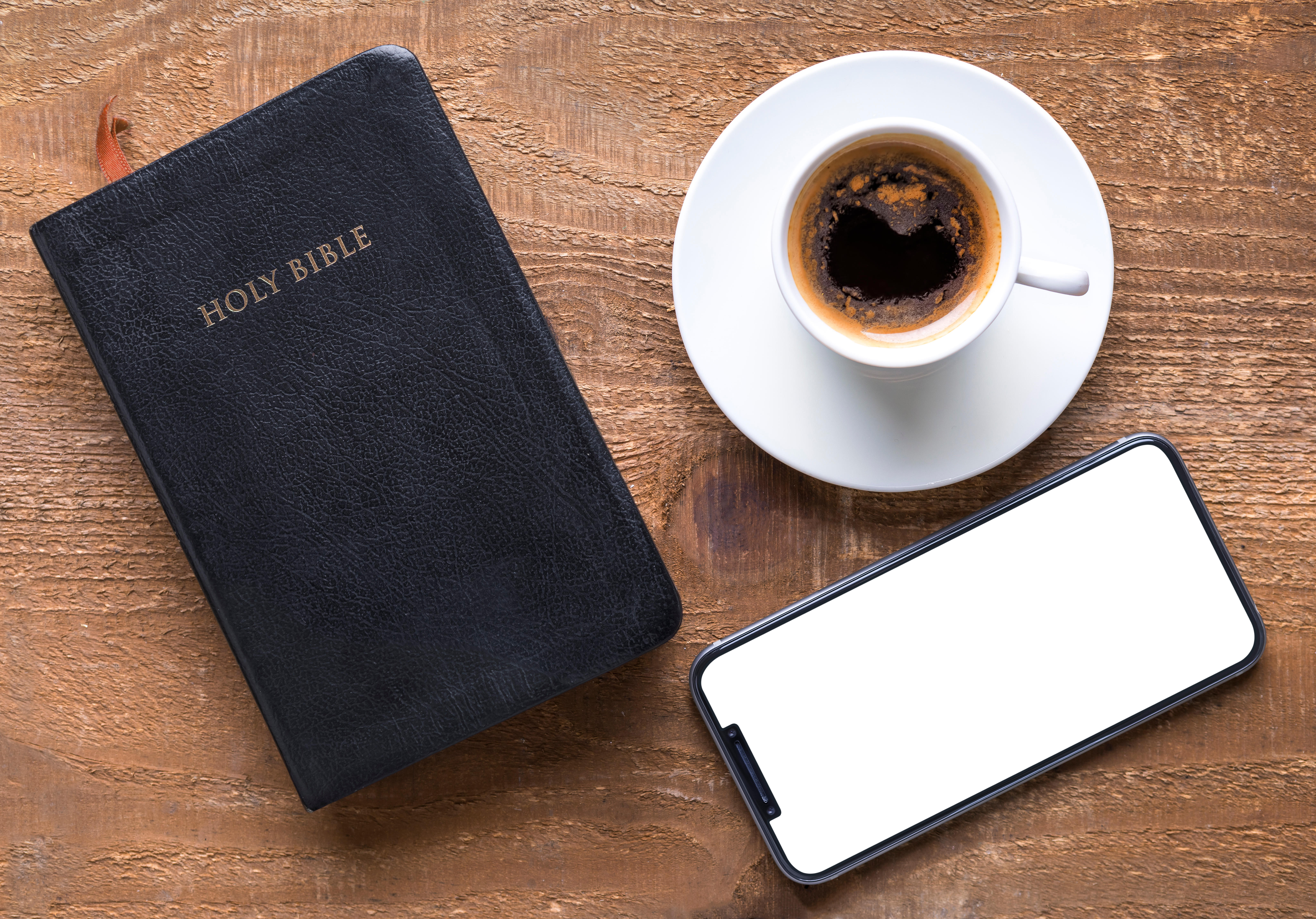 High Angle View Of Coffee Cup With Bible And Mobile Phone On Wooden Table
