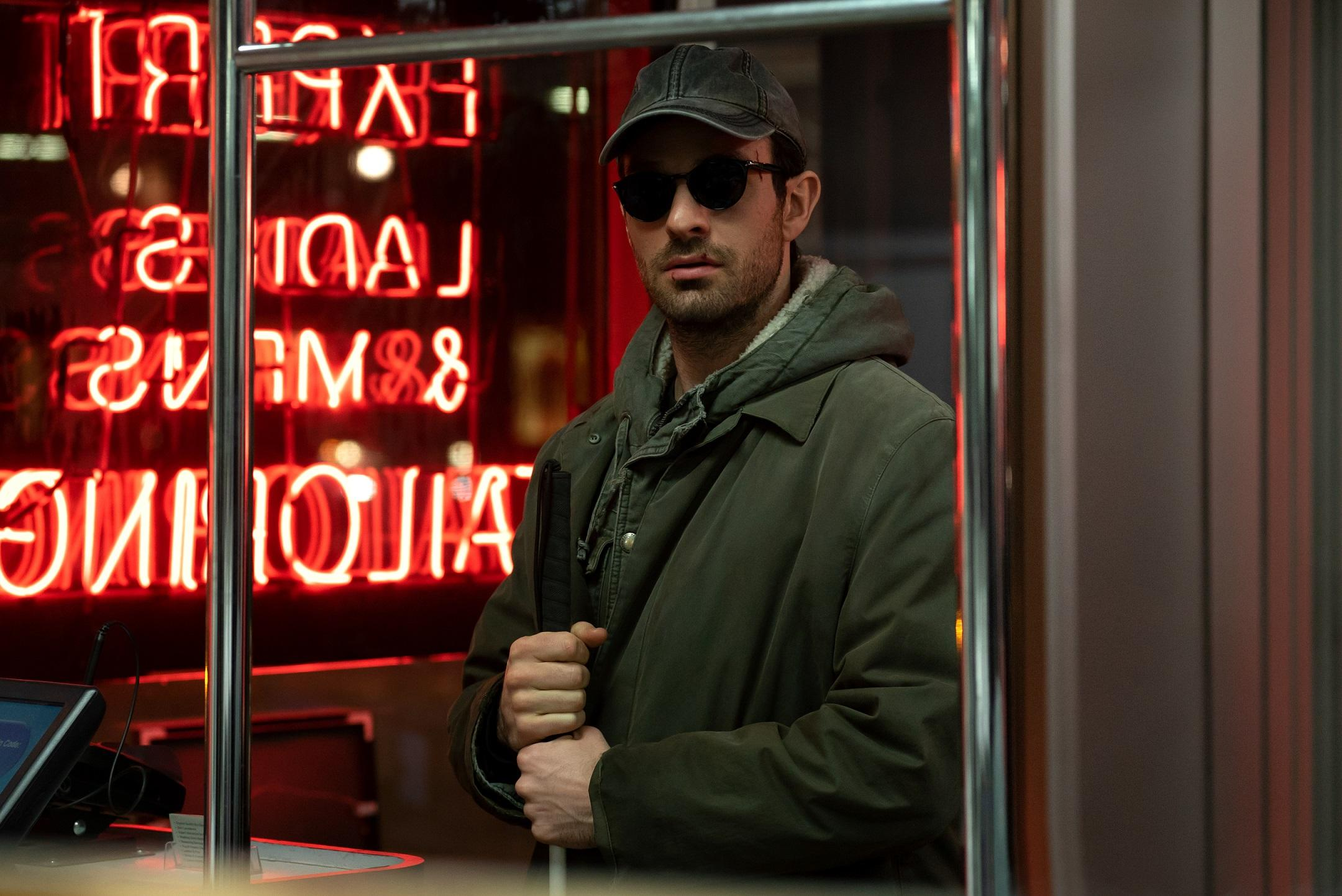 The character of Daredevil stand in front of a neon sign holding his walking cane.