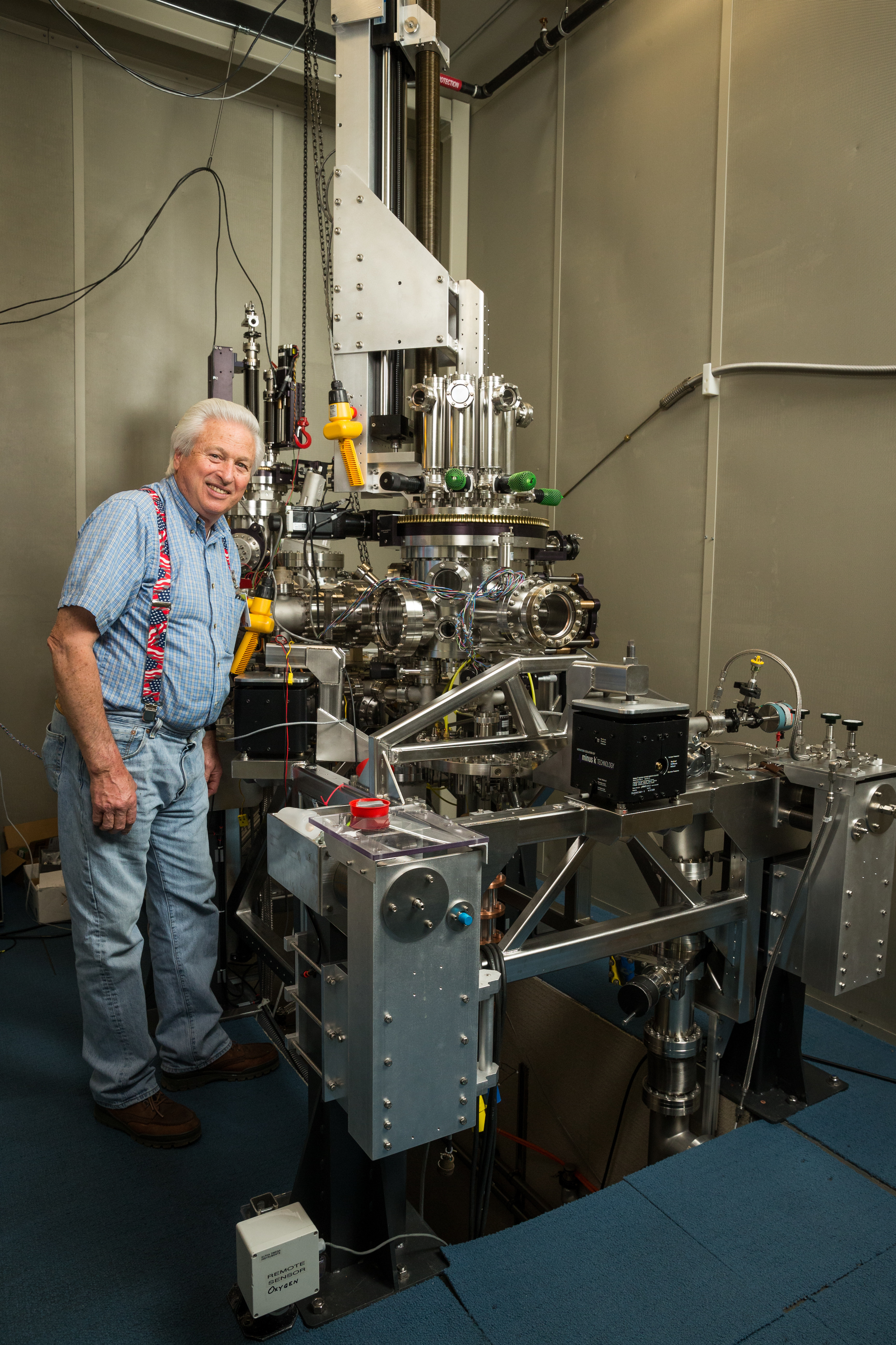 IBM can store a bit of data on a single atom, but the scanning tunneling microscope needed to do so is vastly larger. Here IBM microscope mechanic Bruce Melior stands by the device.