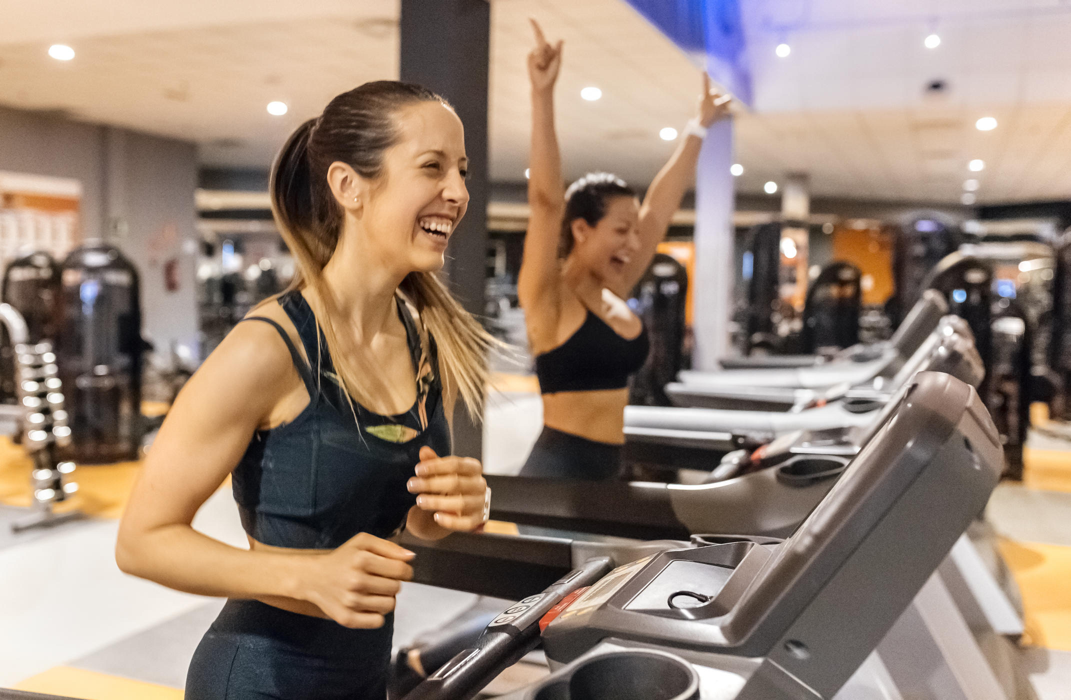 Two happy women working out in gym on a treadmill