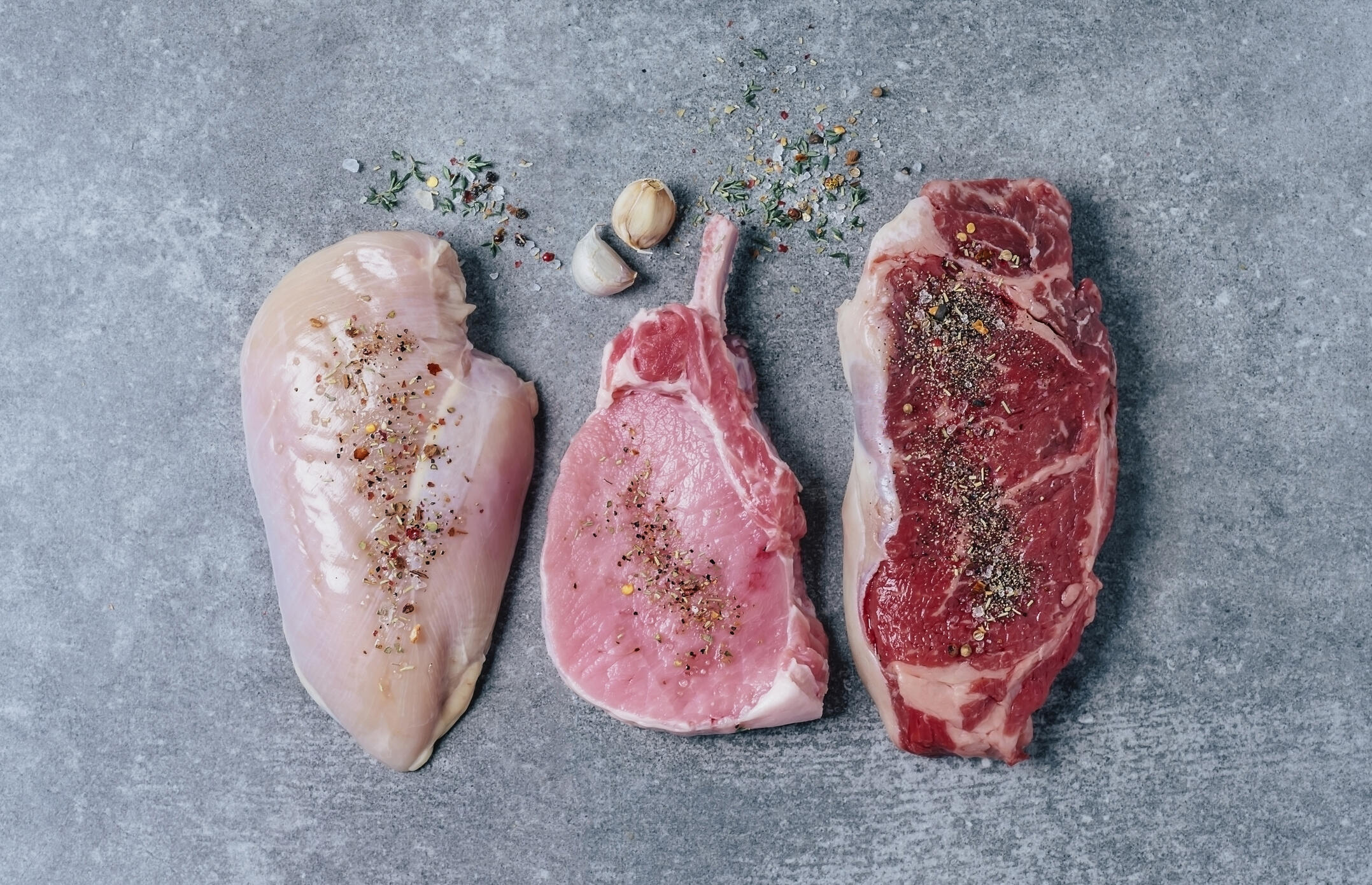 cuts of chicken, pork, and beef on a gray countertop