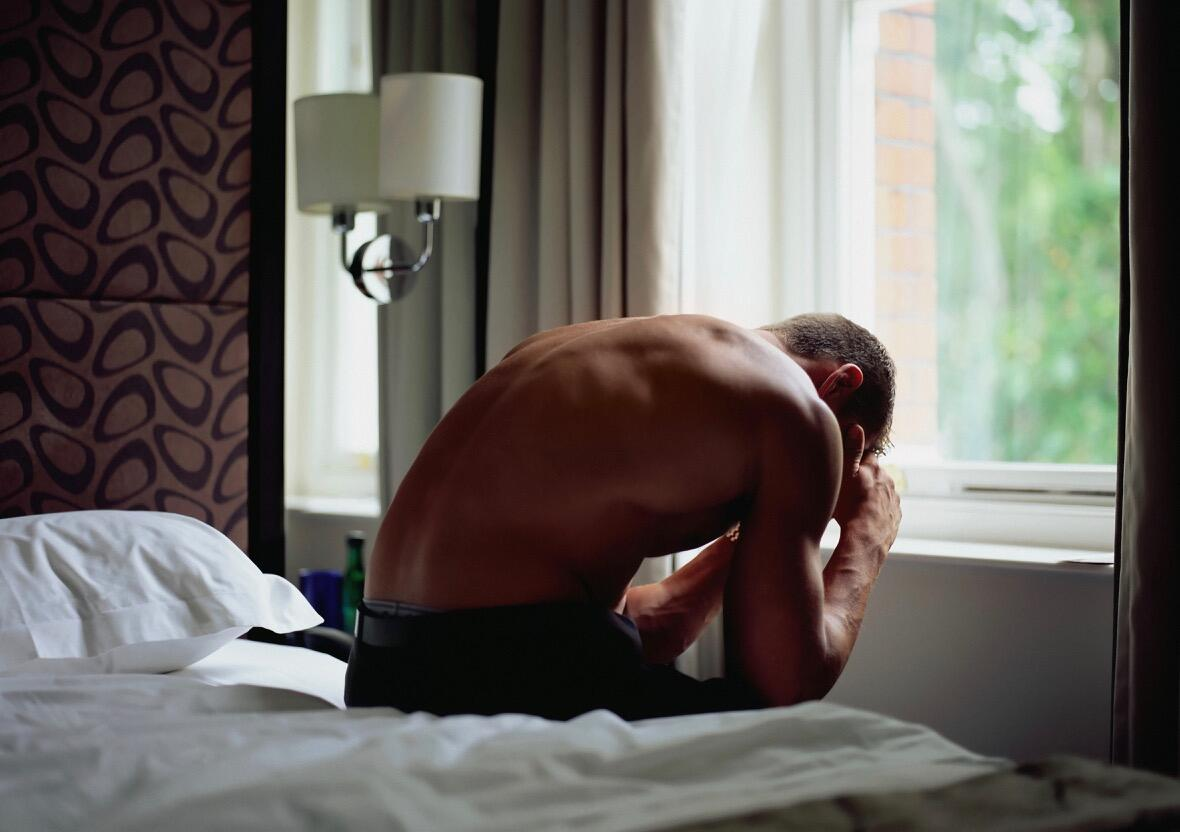 Shirtless man sitting on the edge of a bed, hunched over in thought
