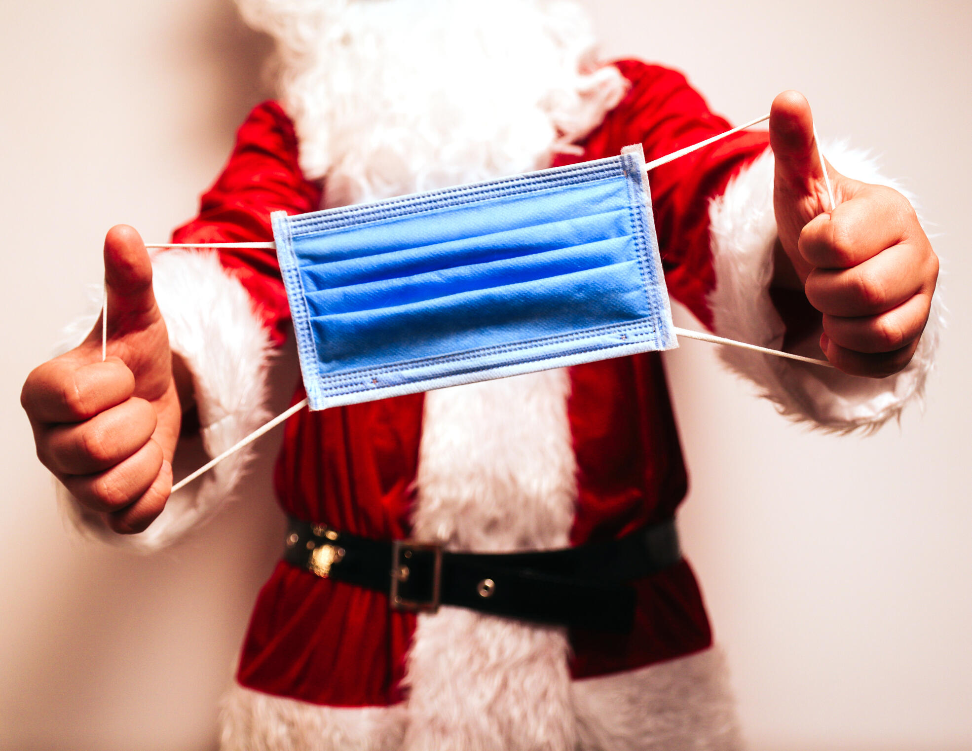 A costumed santa holding out a disposable surgical mask