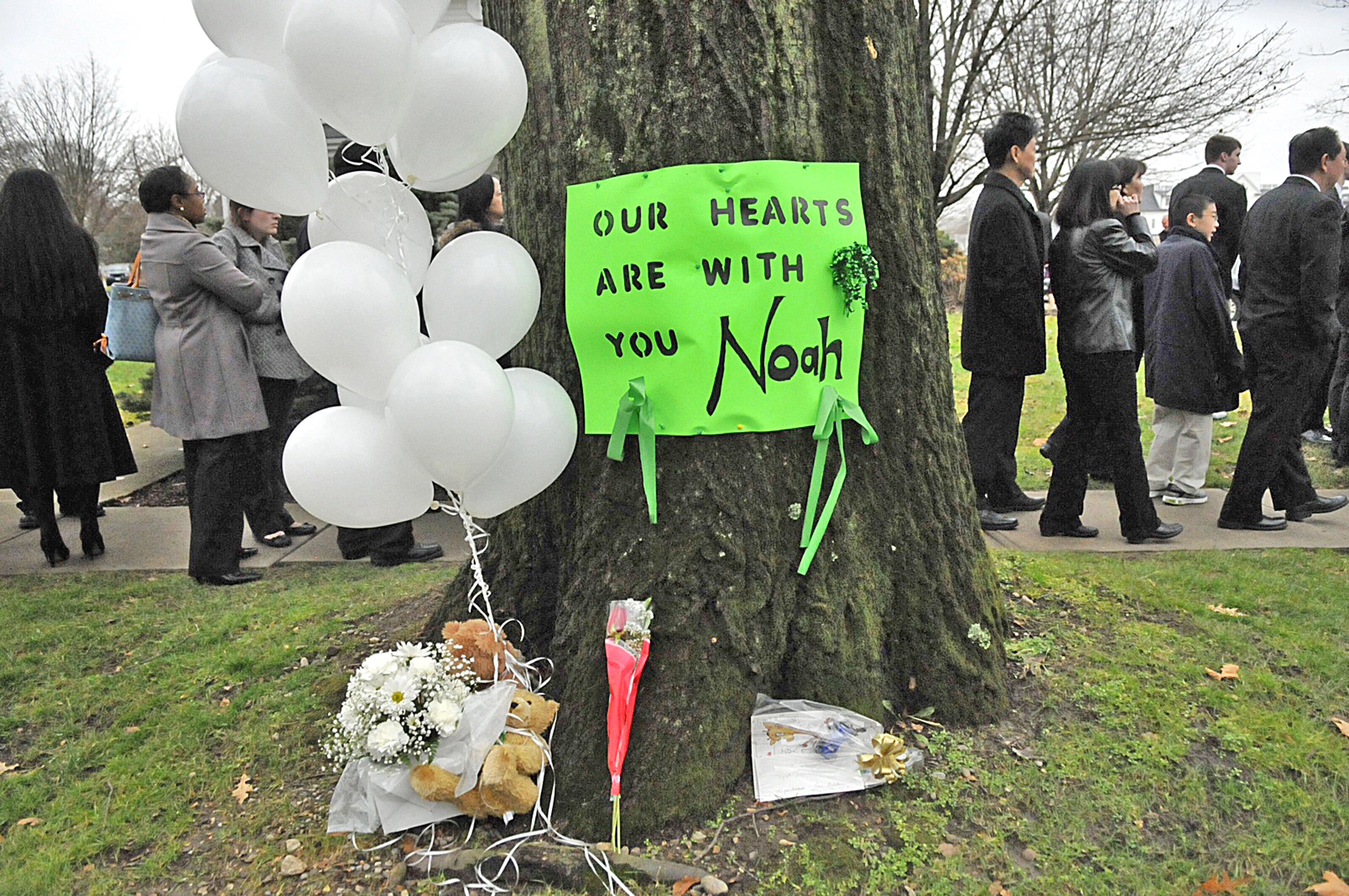 On December 12, 2012, a green poster on a tree memorializes Noah Pozner, a 6-year-old killed in the Sandy Hook school shooting.