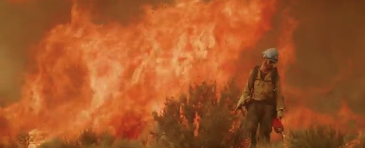 A Carson Hotshot with a wildfire in the background