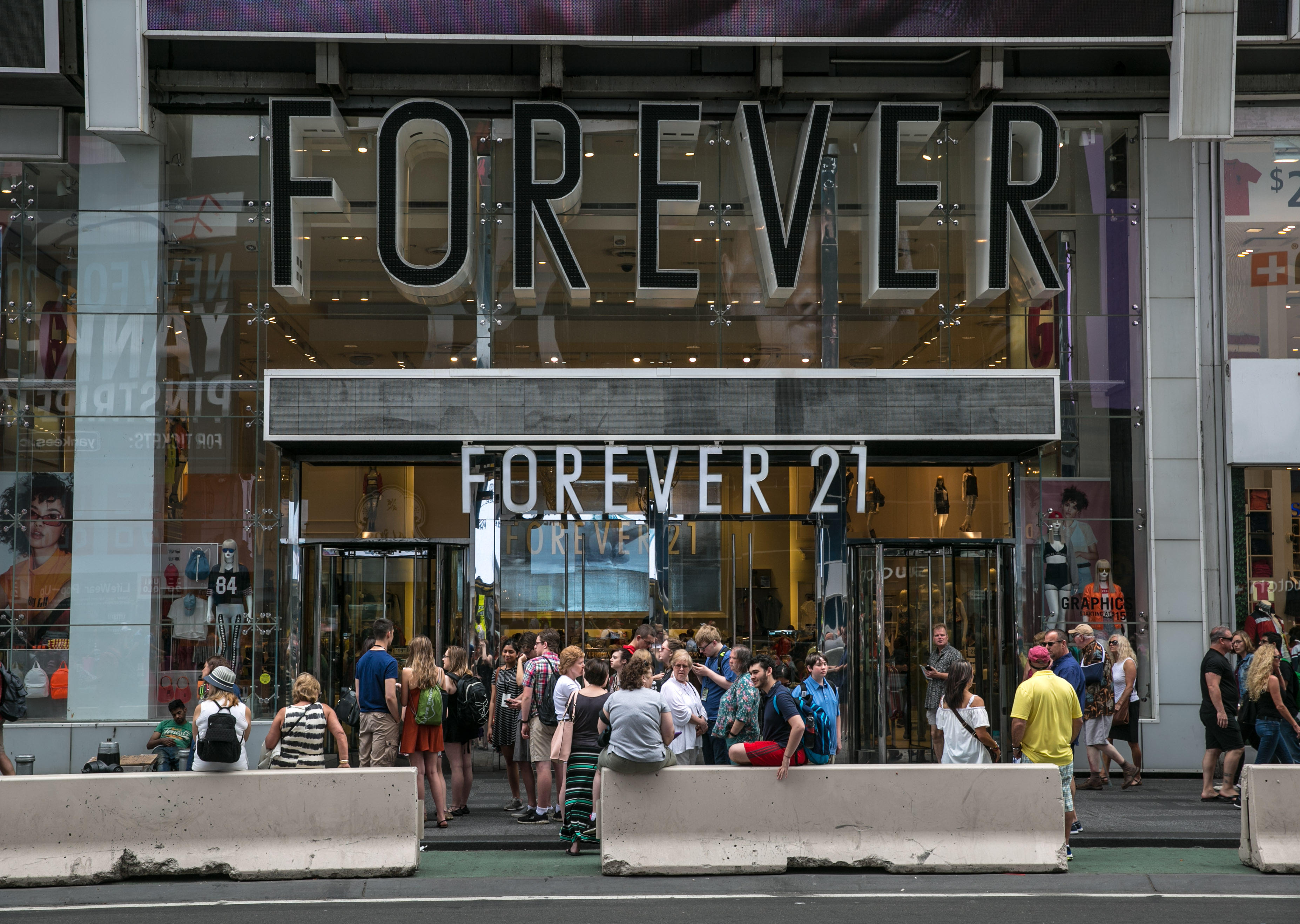 A crowd of people gather outside the Forever 21 store in Times Square in New York City in 2017. The retailer said Thursday hackers infiltrated some point of sales machines at its stores throughout the country.