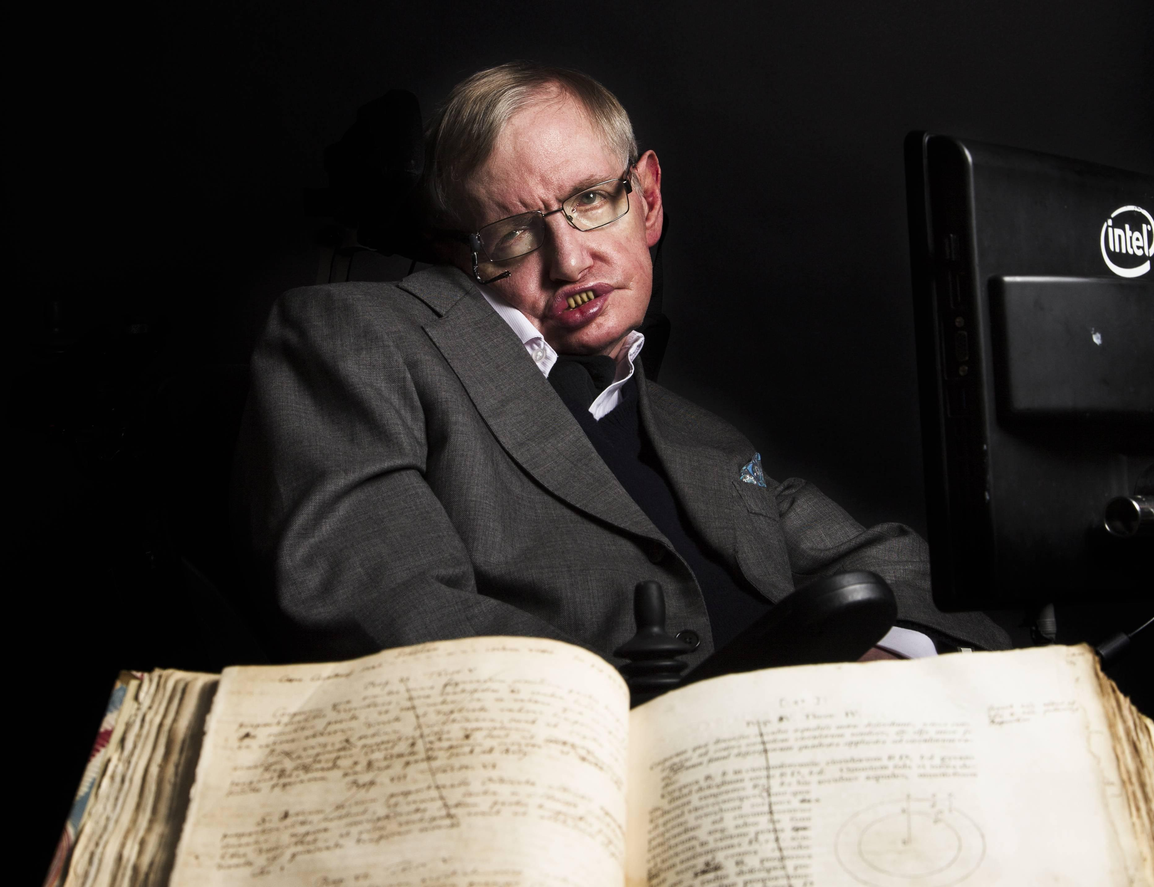 """<p>Stephen Hawking, who died in 2018, is pictured with Isaac Newton's own annotated copy of """"Principia Mathematica.""""</p>"""