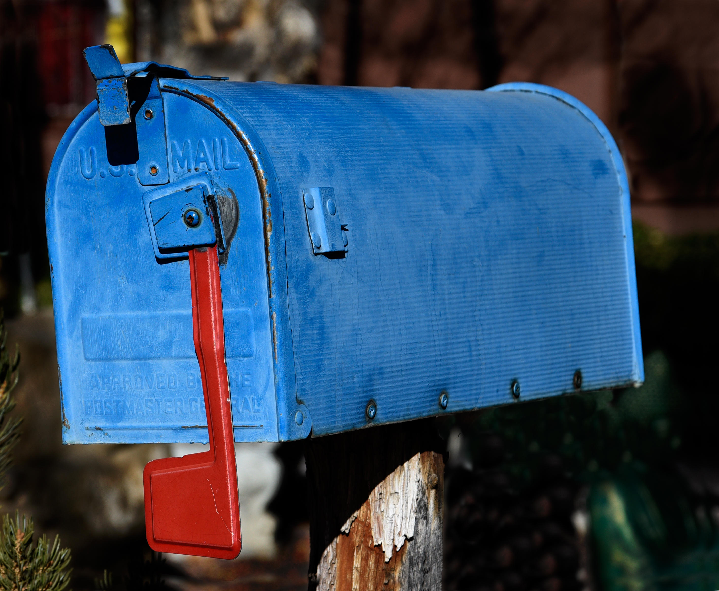 A blue mailbox with a red flag pointed down.