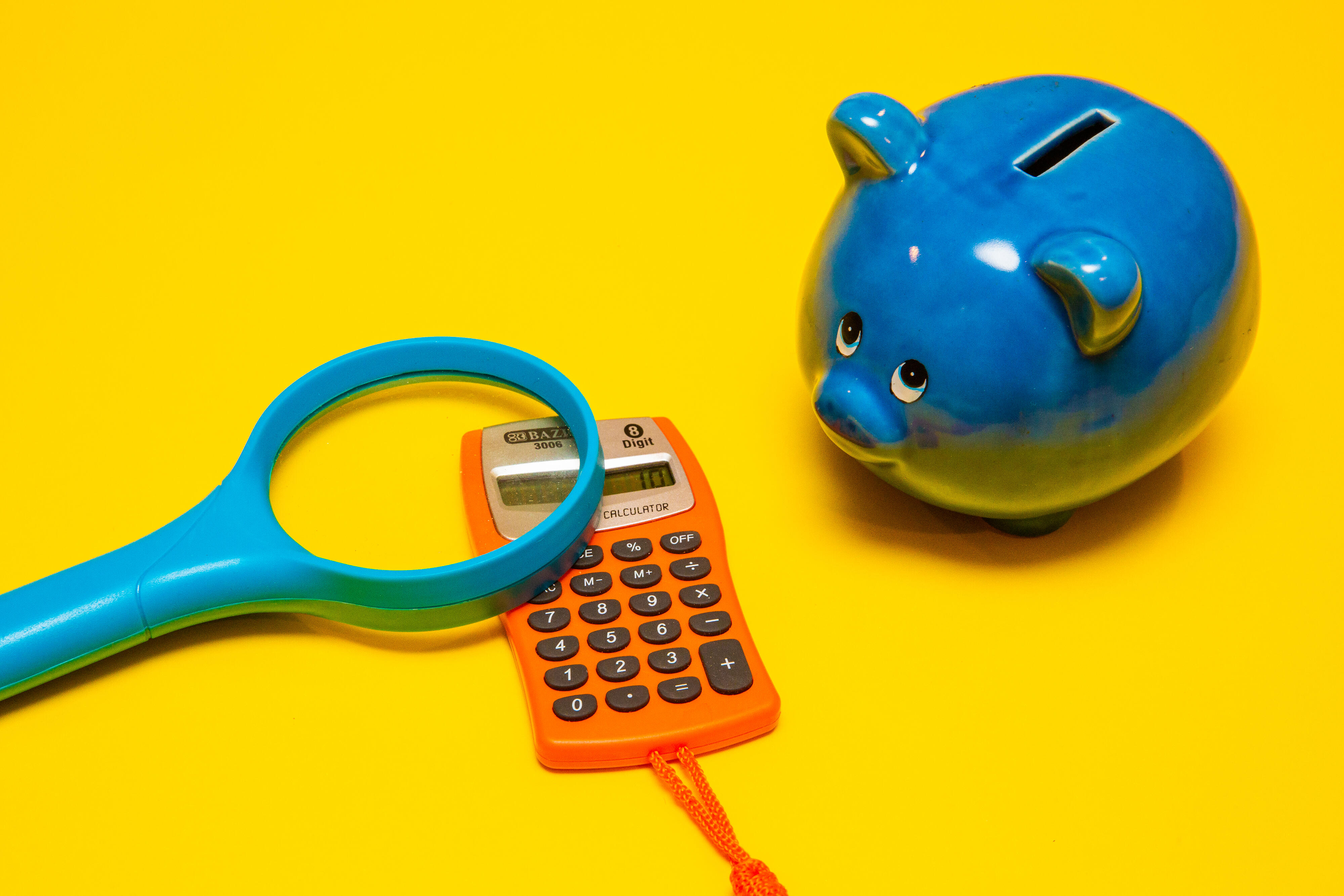 piggy bank, calculator and magnifying glass