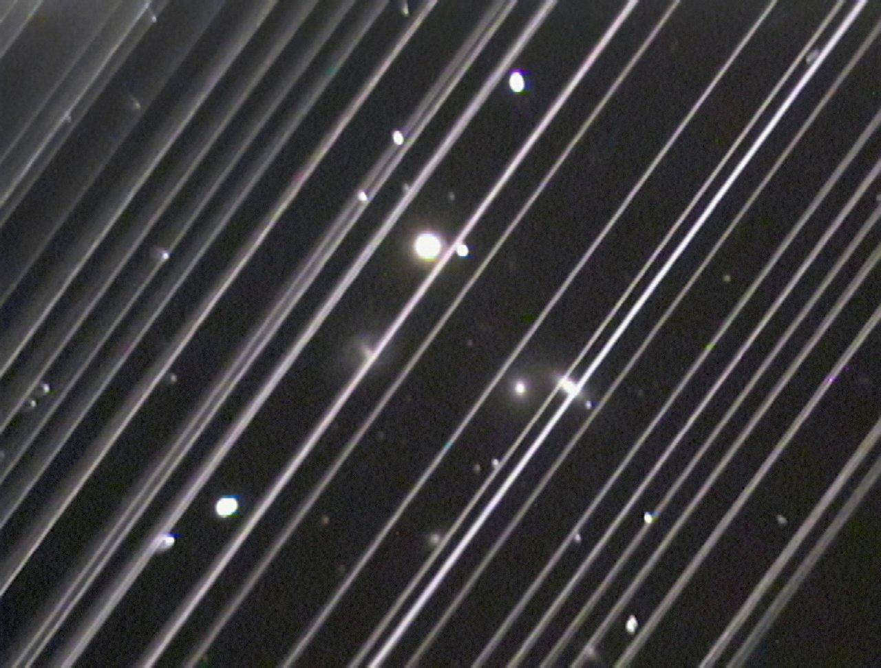 <p>This image of a distant galaxy group from Arizona's Lowell Observatory is marred by diagonal lines from the trails of Starlink satellites shortly after their launch in May.</p>