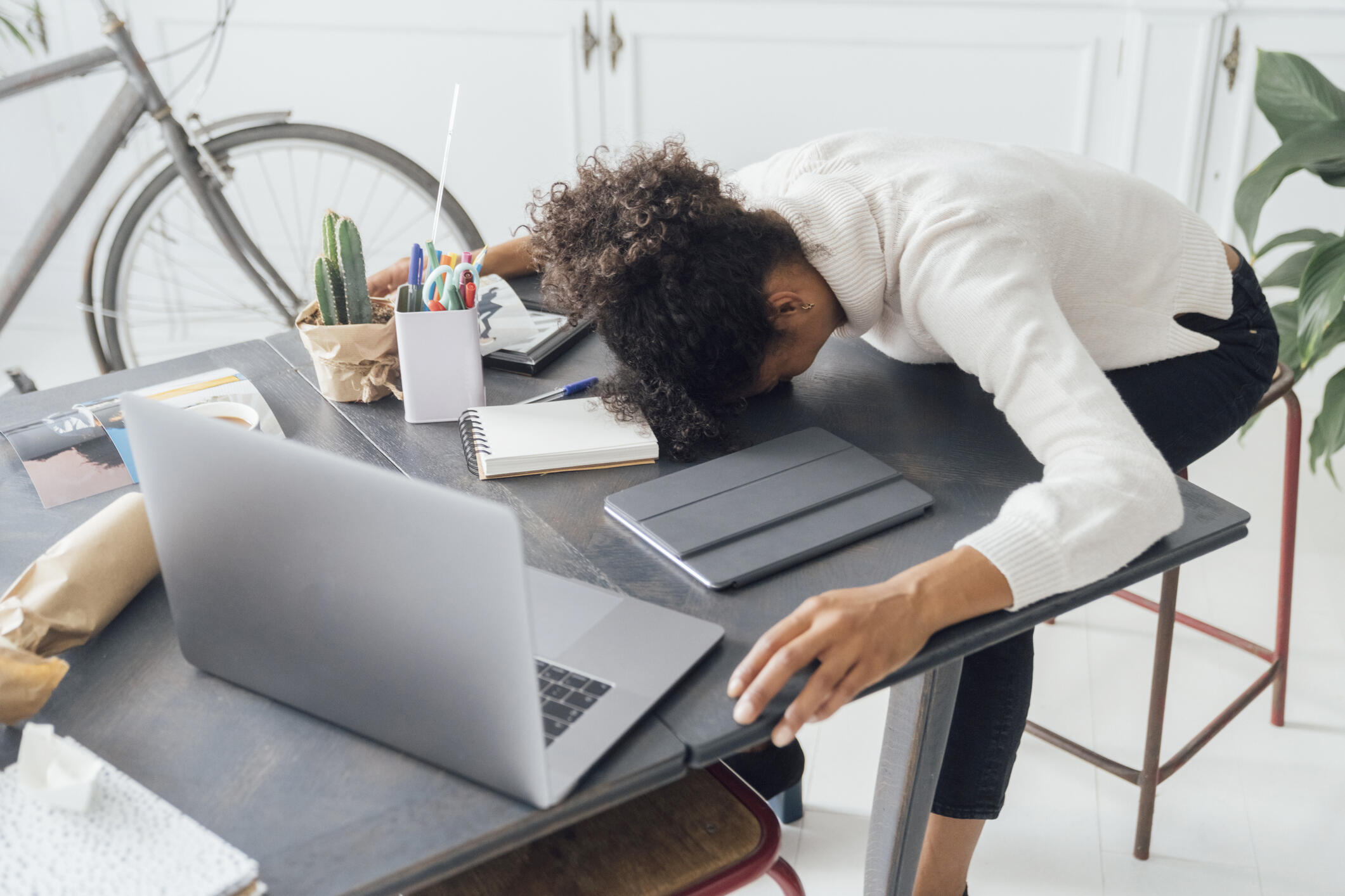 A dark-haired woman in a white shirt slumps over her desk, feeling stressed.