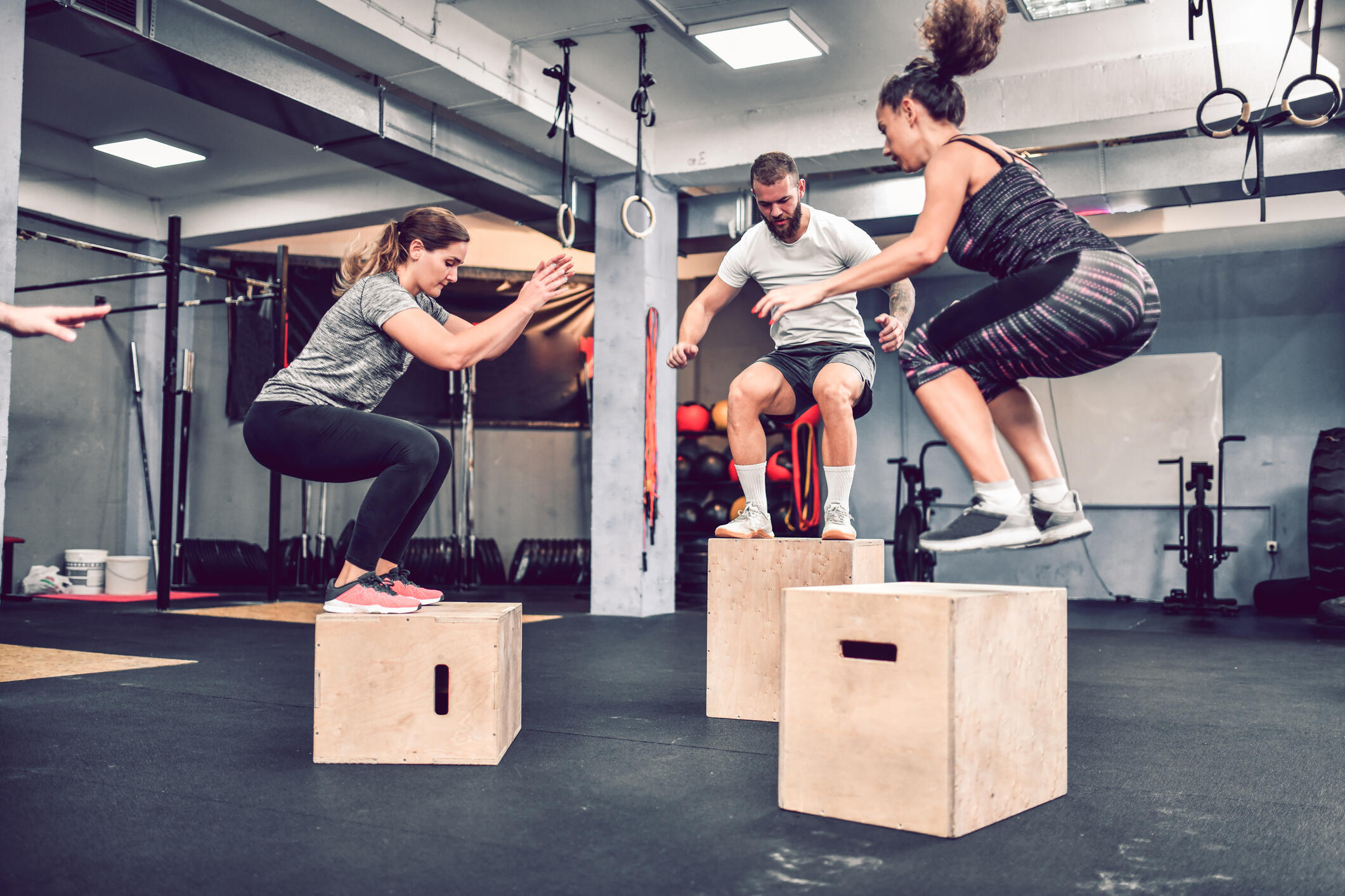 three people in a group fitness class do jumps
