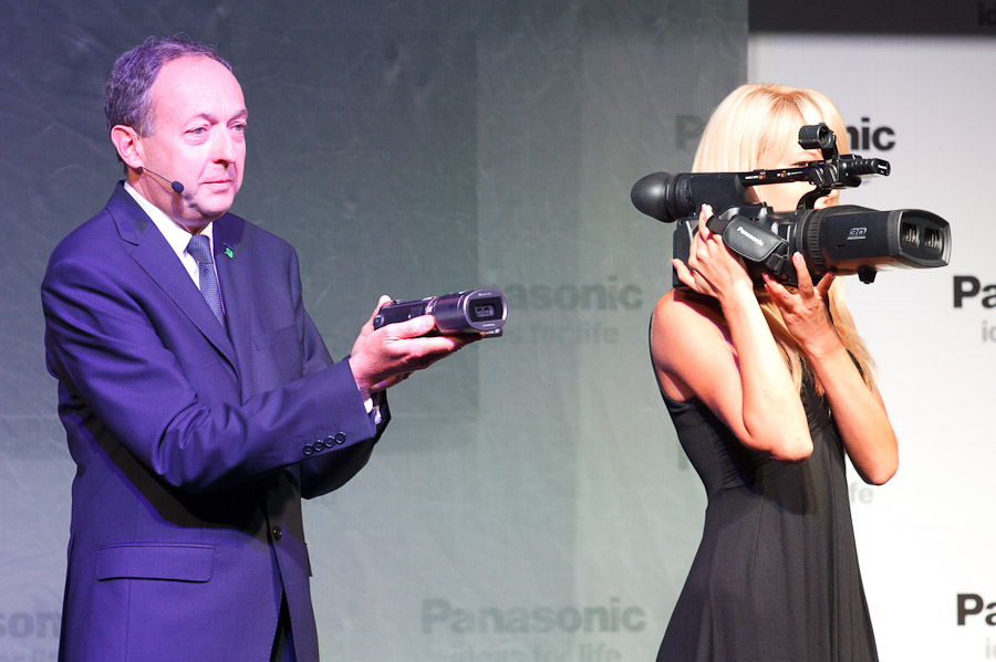 Laurent Abadie, chief executive of Panasonic Europe, shows the company's new 3D-capable camcorder while a model holds one of the company's professional videocameras.