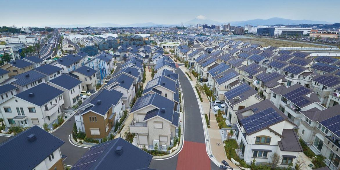 Rows of houses with photovoltaic panels on their roofs.