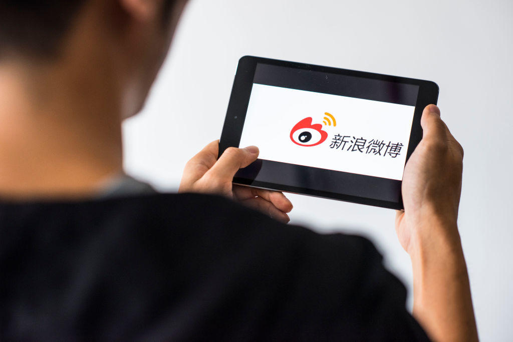 Young man holds a smart device while using Weibo app