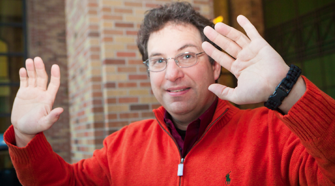 """Is Kevin Mitnick saying """"don't shoot?"""" No. He's just showing off a bracelet that doubles as a handcuff lock pick."""