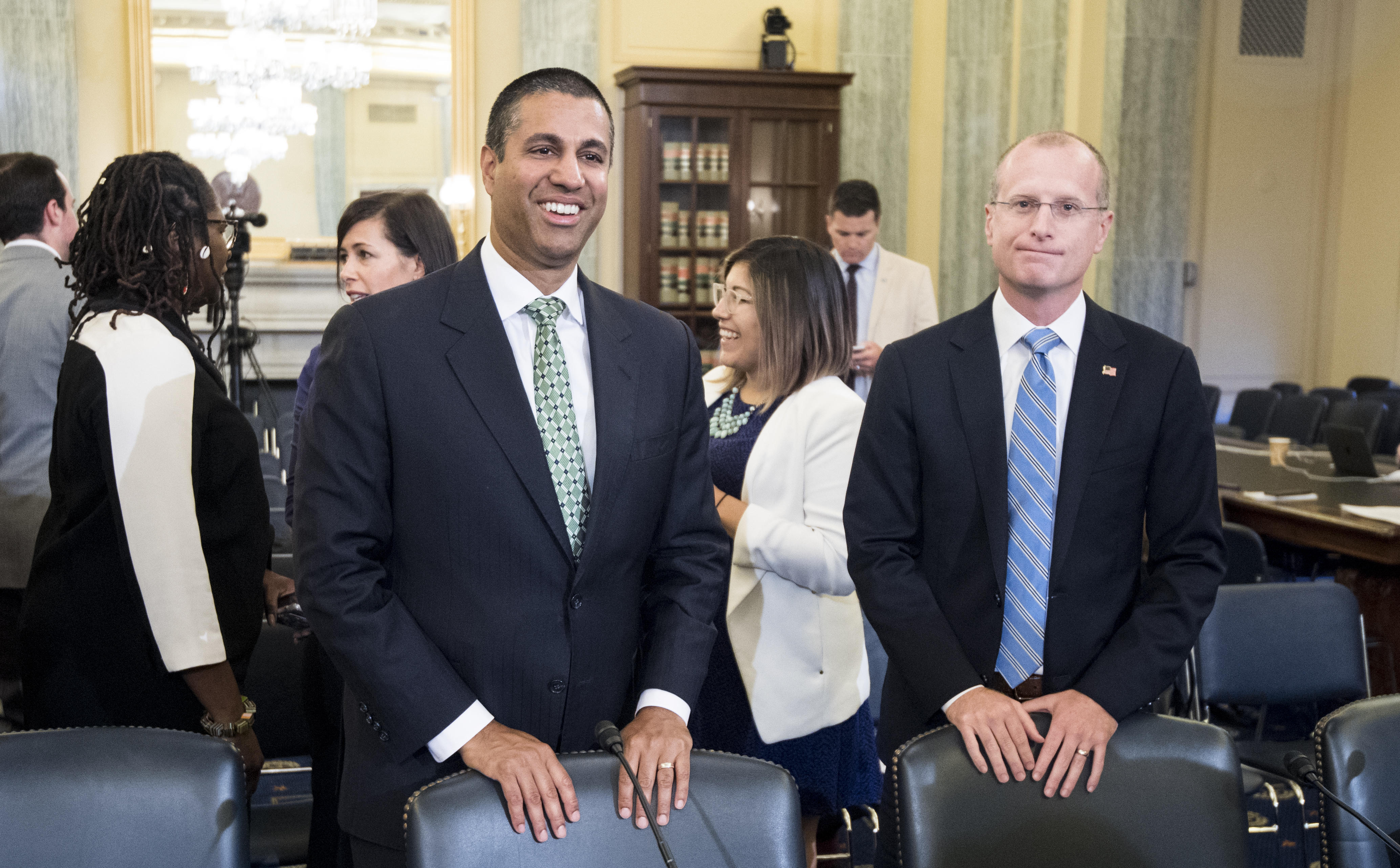 FCC Chairman Ajit Pai (left) and FCC Commissioner Brendan Carr talk before the start of the Senate Committee on Commerce, Science and Transportation hearing on Thursday.