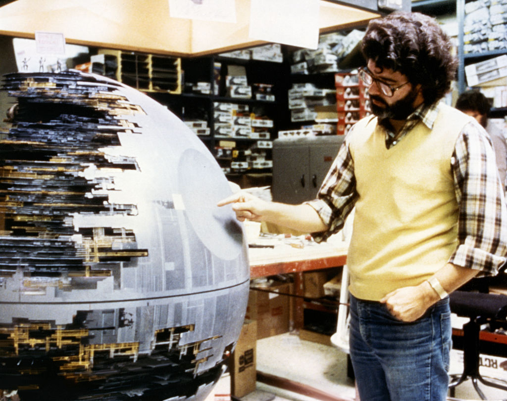 <p>Star Wars writer, director and producer George Lucas with a model of the menacing Death Star, one of the many miniatures built by ILM for the spacefaring saga.</p>